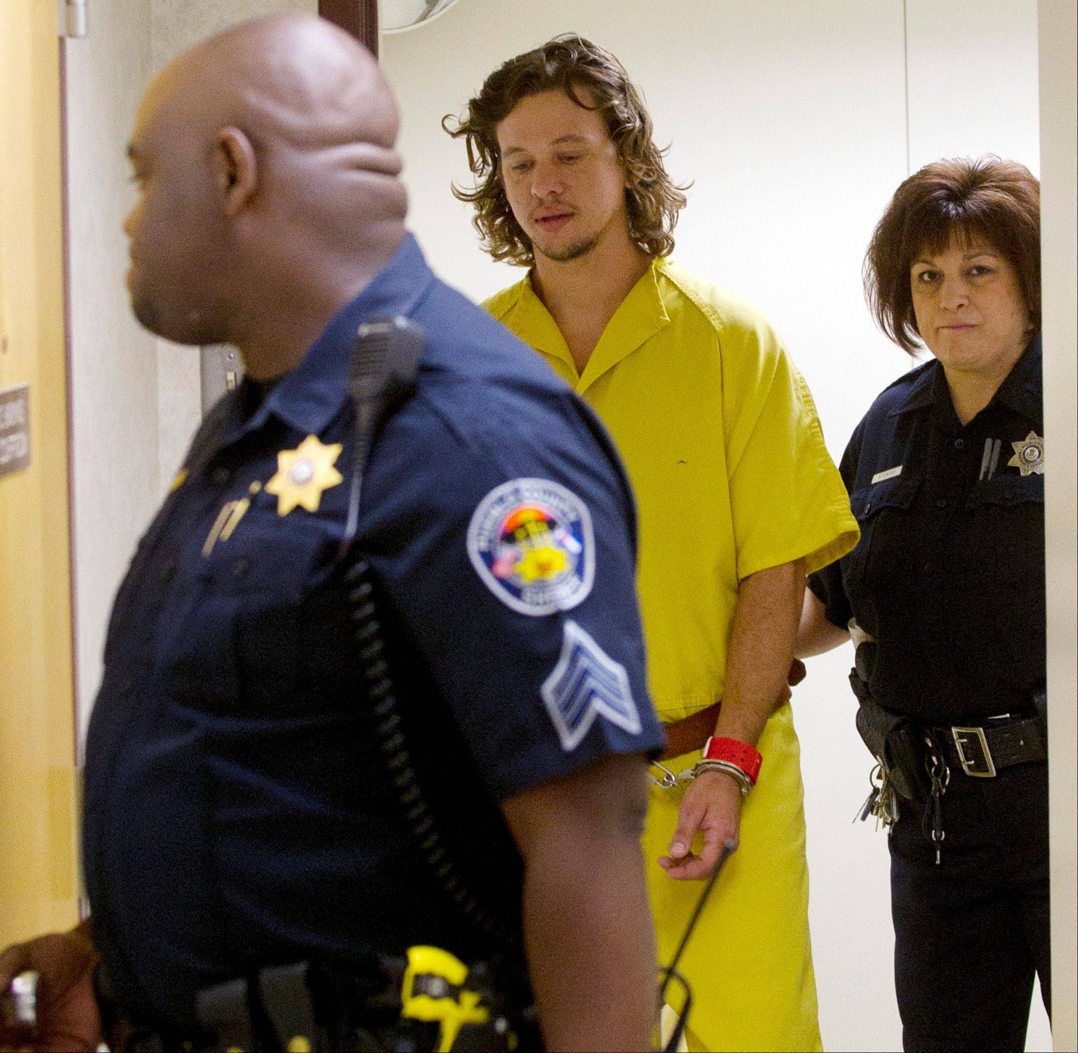 Dylan Dougherty-Stanley is escorted to court in Pueblo, Colo., on Monday. The filing of charges against the three fugitive siblings captured in Colorado has been delayed until next week.
