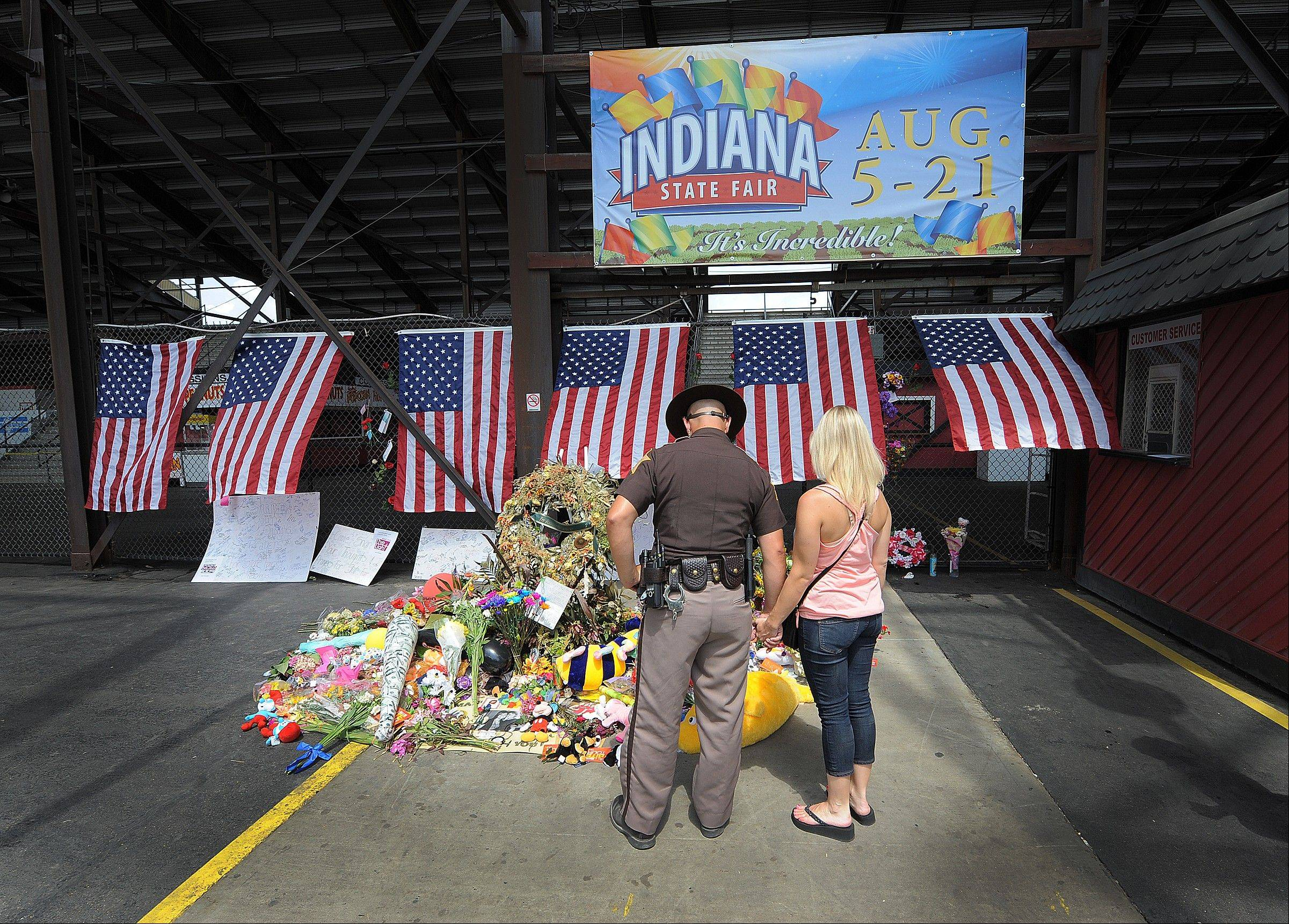 Fairgoers stop and pay their respects at the make-shift memorial for the six victims of last Saturday night stage collapse just before Sugarland was to perform. Police say a 24-year-old woman from Ohio has become the seventh person to die from injuries when a stage collapsed at the Indiana State Fair.
