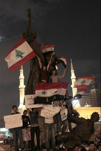 Syrian protesters stand on the Martyrs statue wave Lebanese and Syrian flags during a vigil sit-in held by Lebanese intellectuals and journalists against the Syrian regime and to show their support to the protesters who demonstrate against the Syrian President Bashar Assad.
