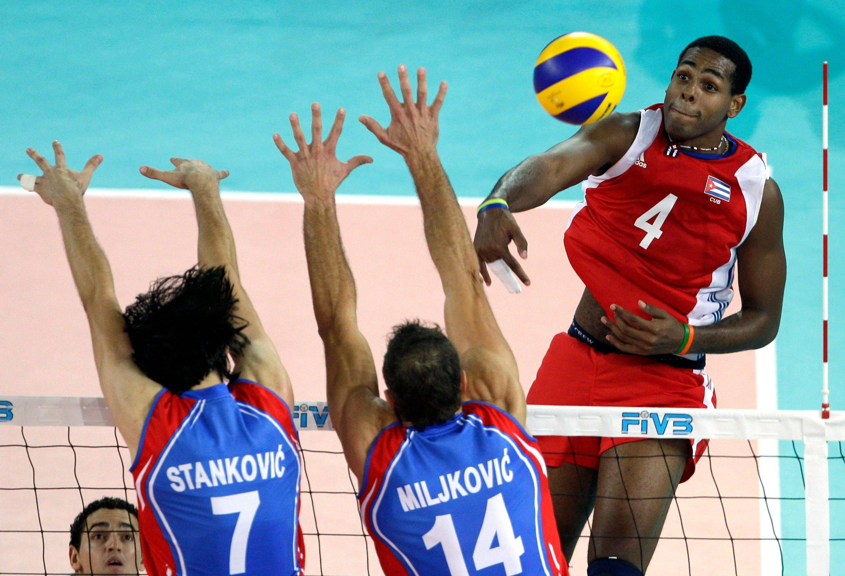 Cuba's Joandry Leal Hidalgo, right, spikes the ball past Serbia's Dragan Stankovic, left, and Ivan Miljkovic at the Men's Volleyball World Championships in Rome, Italy. State newspapers Granma and Juventud Rebelde reported that captain Roberlandy Simon and players Joandry Leal and Raydel Hierrezuelo had quit the national volleyball team that was runner-up at the 2010 World Championship in Italy. The reports said they left the team for personal reasons, but their absence sparked rumors they wanted to defect. Hierrezuelo has since returned to the squad. Cuba has always had a problem keeping talent on the island, but the exodus in sports and entertainment seems to be growing.