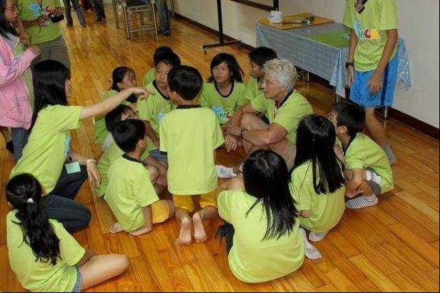 Immanuel Lutheran teacher Sue Domeier huddles up with her students at the Taiwan Children's Center in July. She served as a member of the teaching mission team from Concordia University-Wisconsin to work with kids in Taiwan.