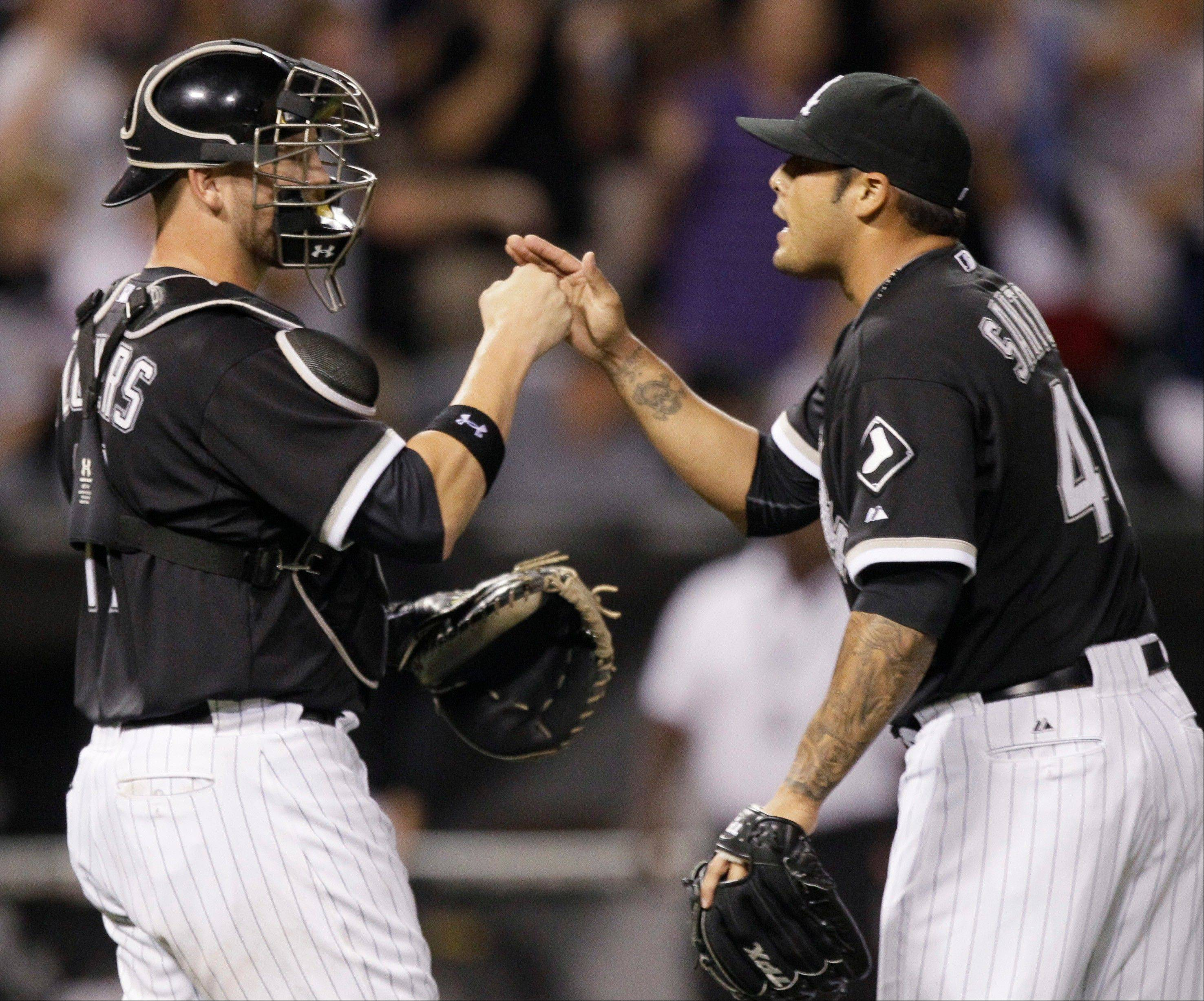 "White Sox closer Sergio Santos, right, celebrates with catcher Tyler Flowers after they defeated the Texas Rangers on Saturday. Manager Ozzie Guillen says Flowers has been ""outstanding"" behind the plate."