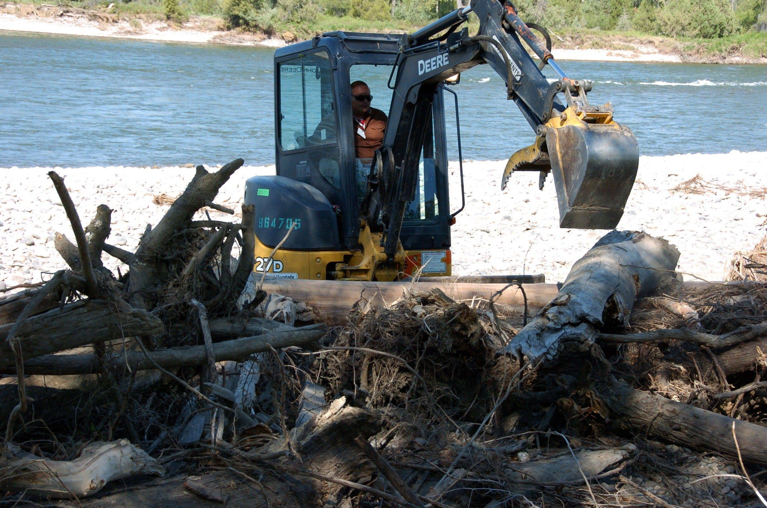 An excavator pulls apart a debris pile along a stretch of the Yellowstone River near Billings, Mont. that was contaminated with oil from a July 1 Exxon Mobil pipeline spill. Hundreds of oil-fouled log jams and debris piles on the river�s banks and islands have slowed cleanup efforts following the 1,000 barrel spill.
