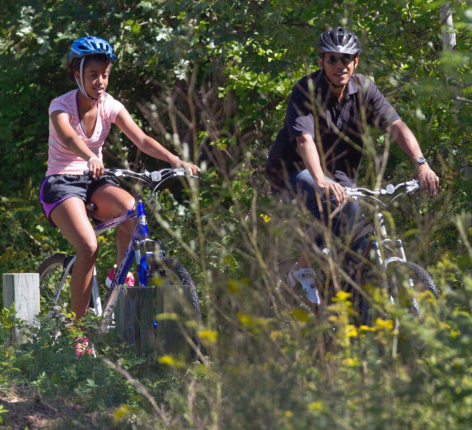 President Barack Obama, and daughter Malia, ride bicycles in Manuel F. Correllus State Forest in West Tisbury, on Martha�s Vineyard, Mass.