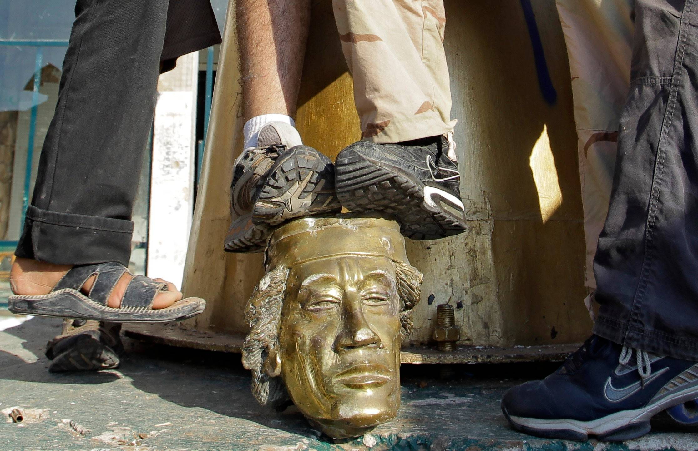 Rebel fighters trample on a head of Moammar Gadhafi inside the main compound in Bab al-Aziziya in Tripoli, LIbya, Tuesday.