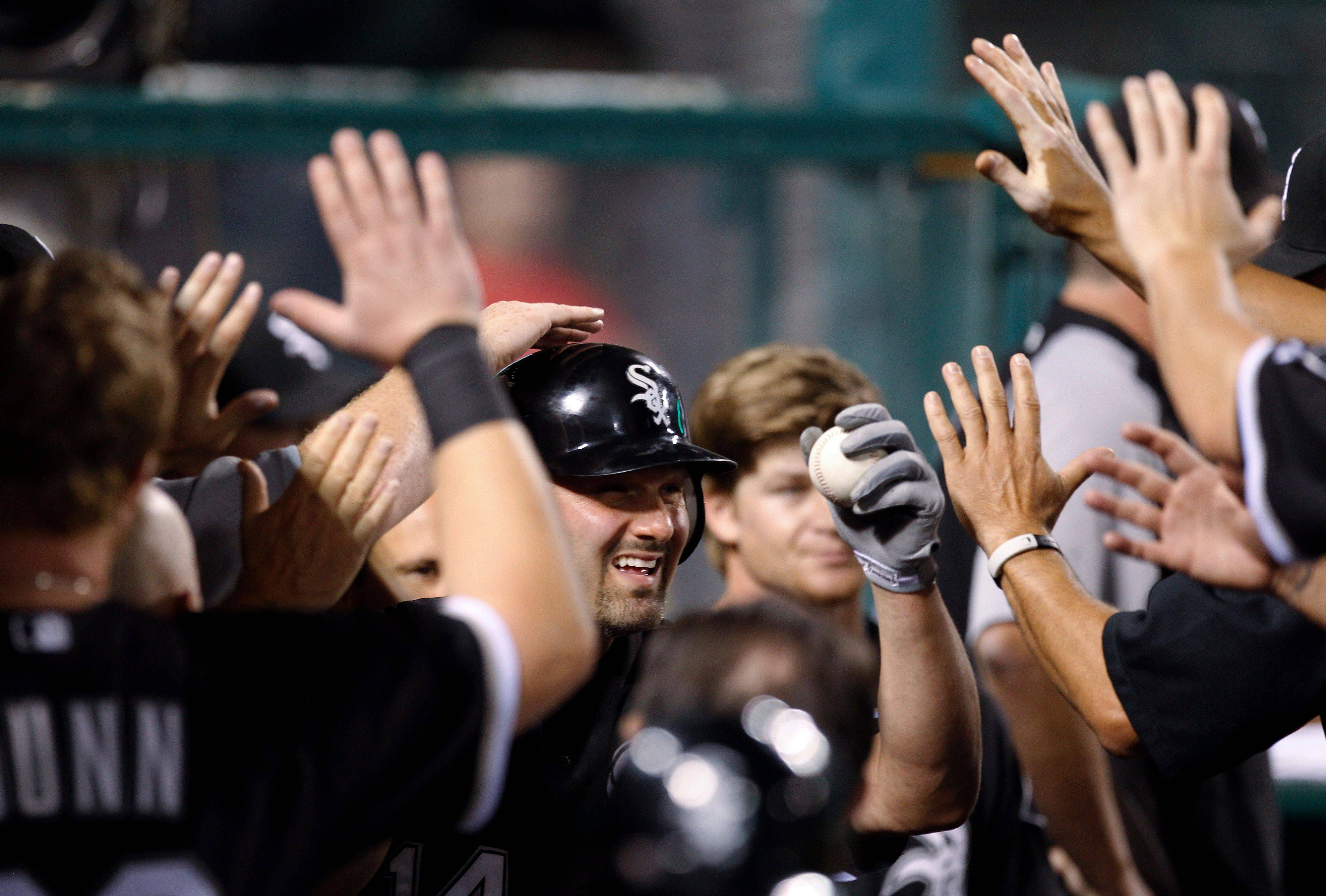 Paul Konerko is greeted in the dugout after his 2,000th career hit during Tuesday night's game. The White Sox lost 5-4.