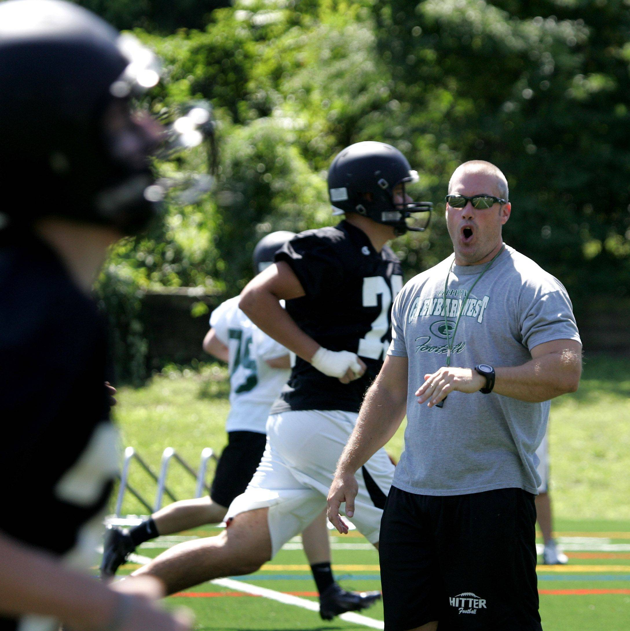 Glenbard West coach Chad Hetlet puts the team through running drills during the first day of football practice on Wednesday in Glen Ellyn.
