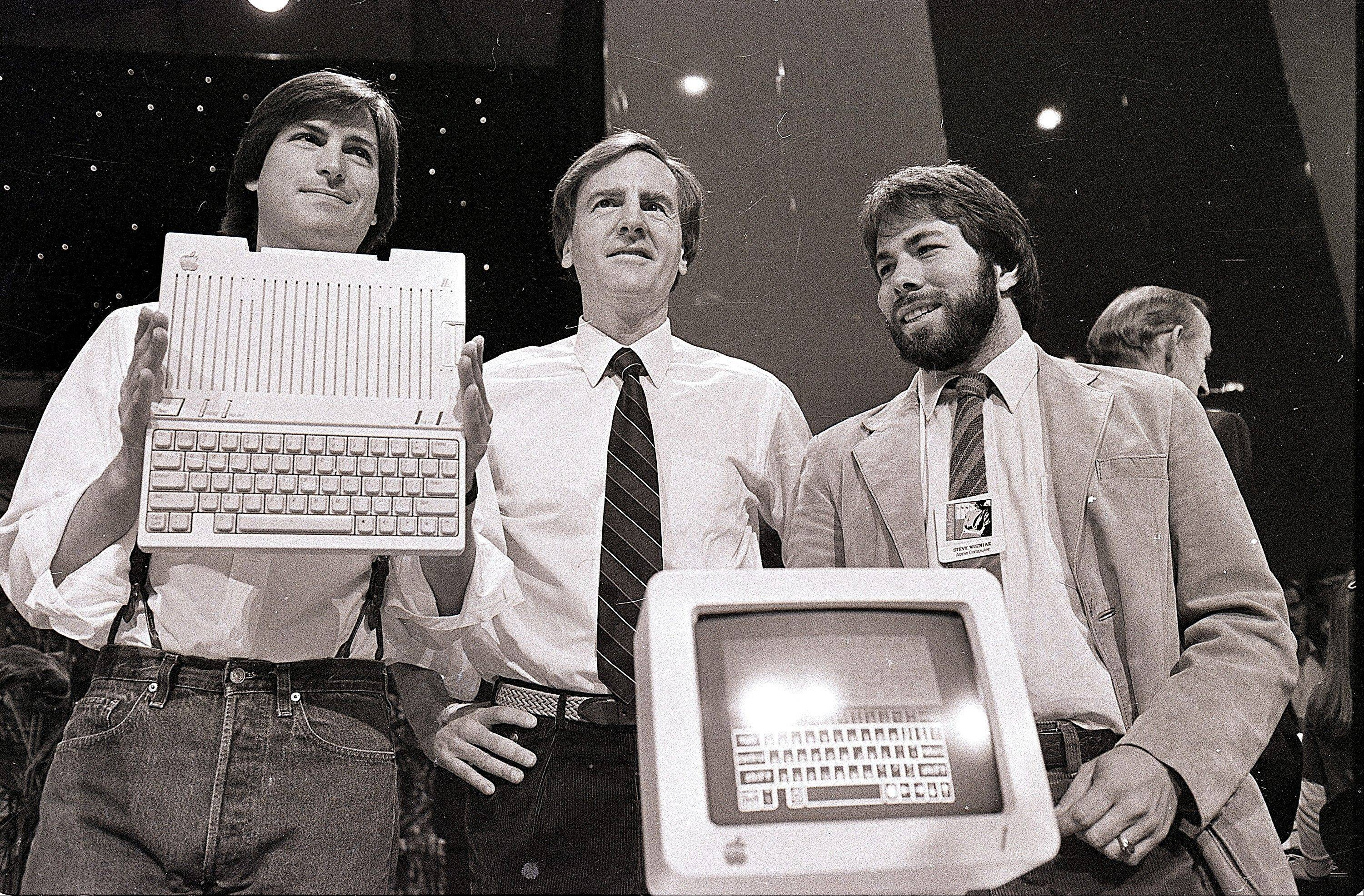 In this April 24, 1984, file photo, Steve Jobs, left, chairman of Apple Computers, John Sculley, center, then president and CEO, and Steve Wozniak, co-founder of Apple, unveil the new Apple IIc computer in San Francisco.