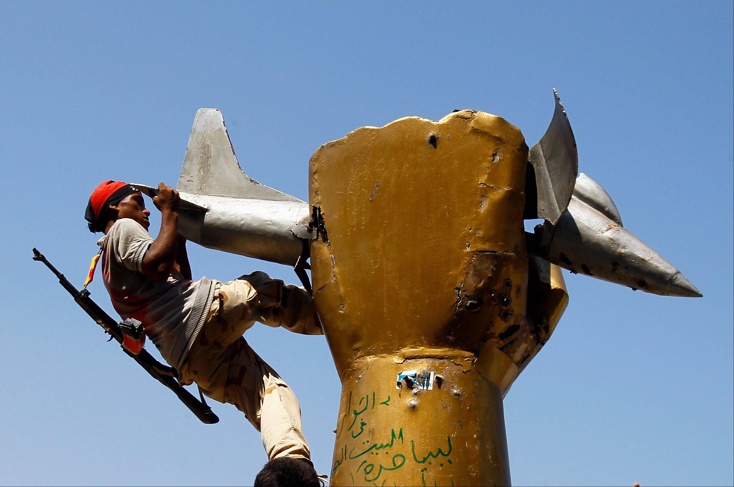 A rebel fighter climbs on top of a statue inside Moammar Gadhafi's compound Bab al-Aziziya in Tripoli early Wednesday.