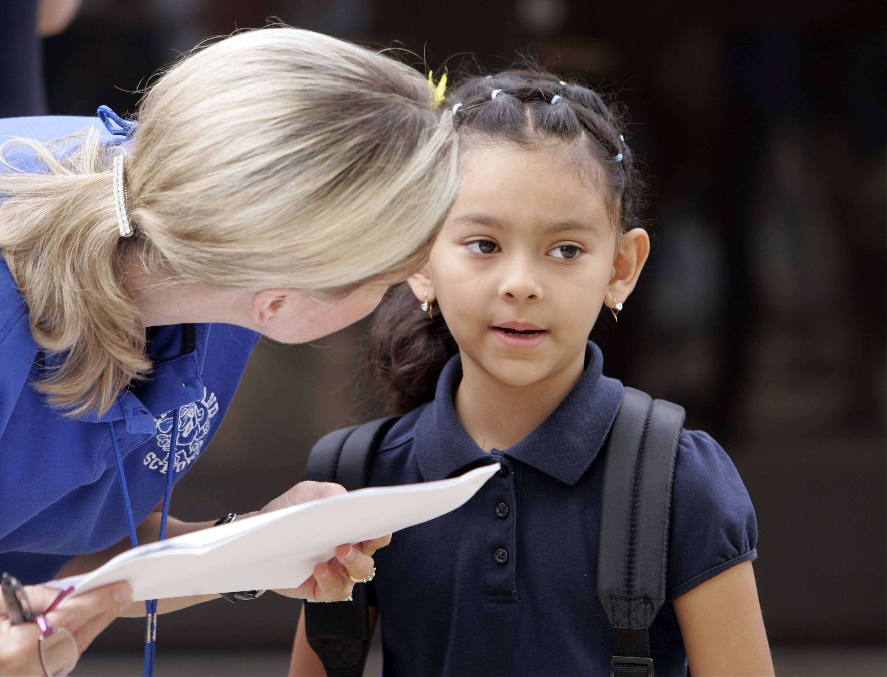 Six-year-old first grade student America Arendondo gets some help finding her class from Lisa Mercado on the first day of school at Highland Elementary School in Elgin Wednesday, August 24, 2011.