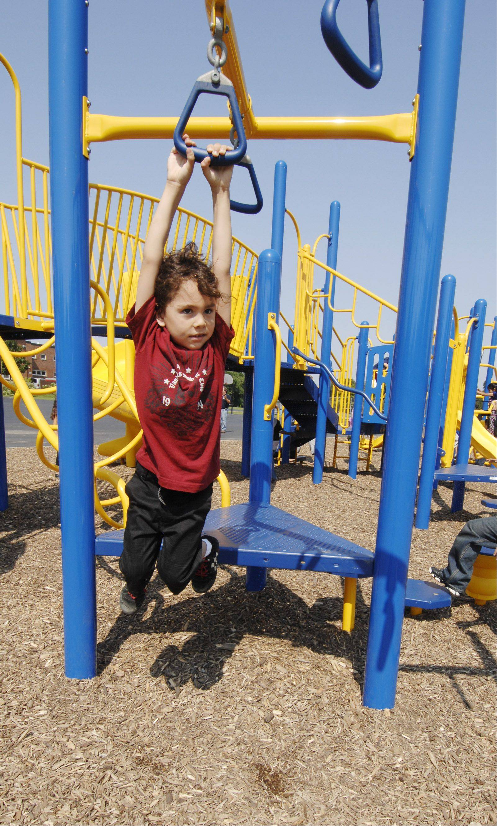 Christian Robles tries out the hand loops on the new playground equipment.