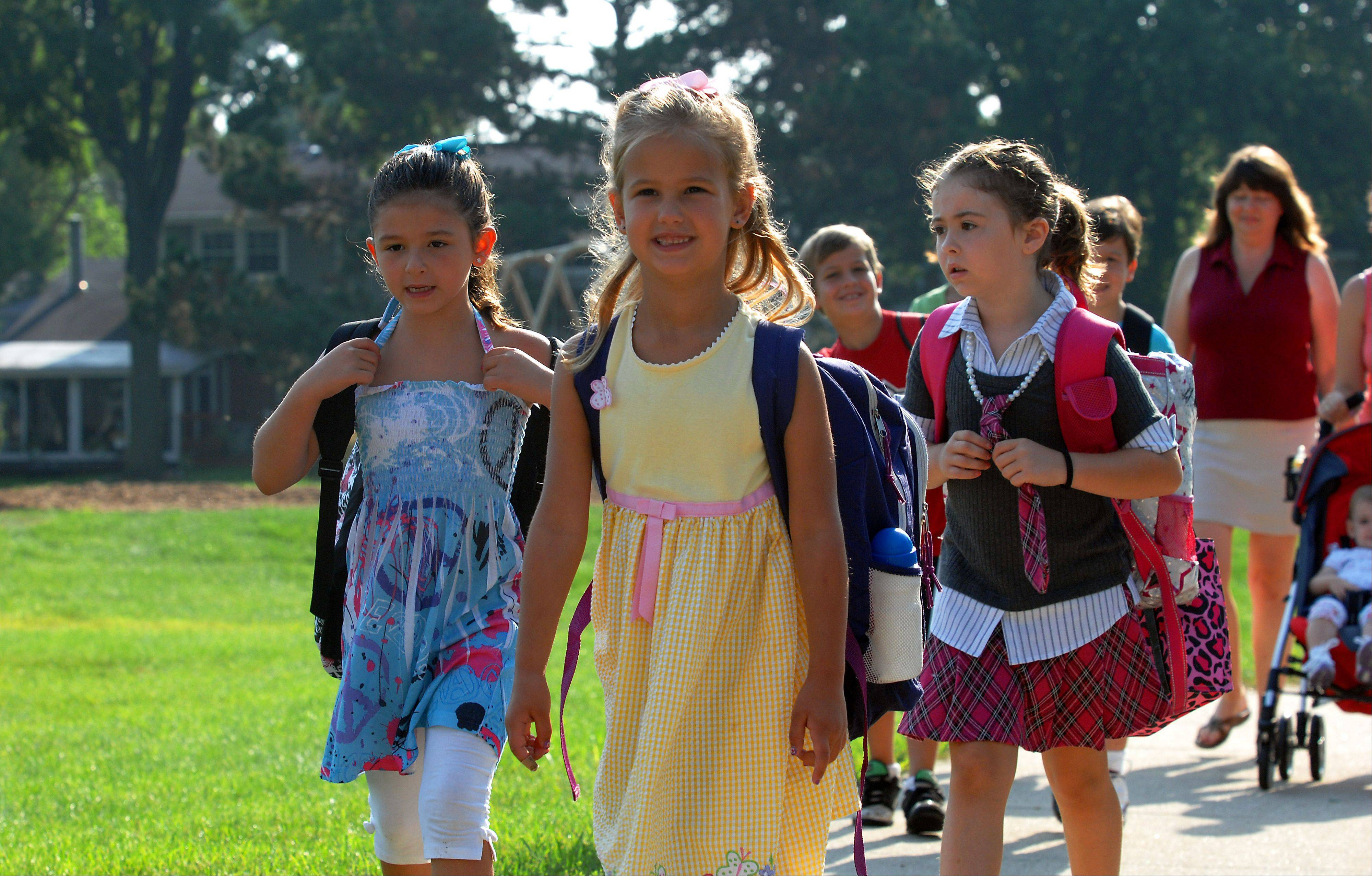 Abby Sprenger, 6, and her friends Gabbi Fontanetta, 7, left and Viktoria Velikova, 7, head to their first day of class at Salt Creek Elementary School in Elk Grove Village on Wednesday.
