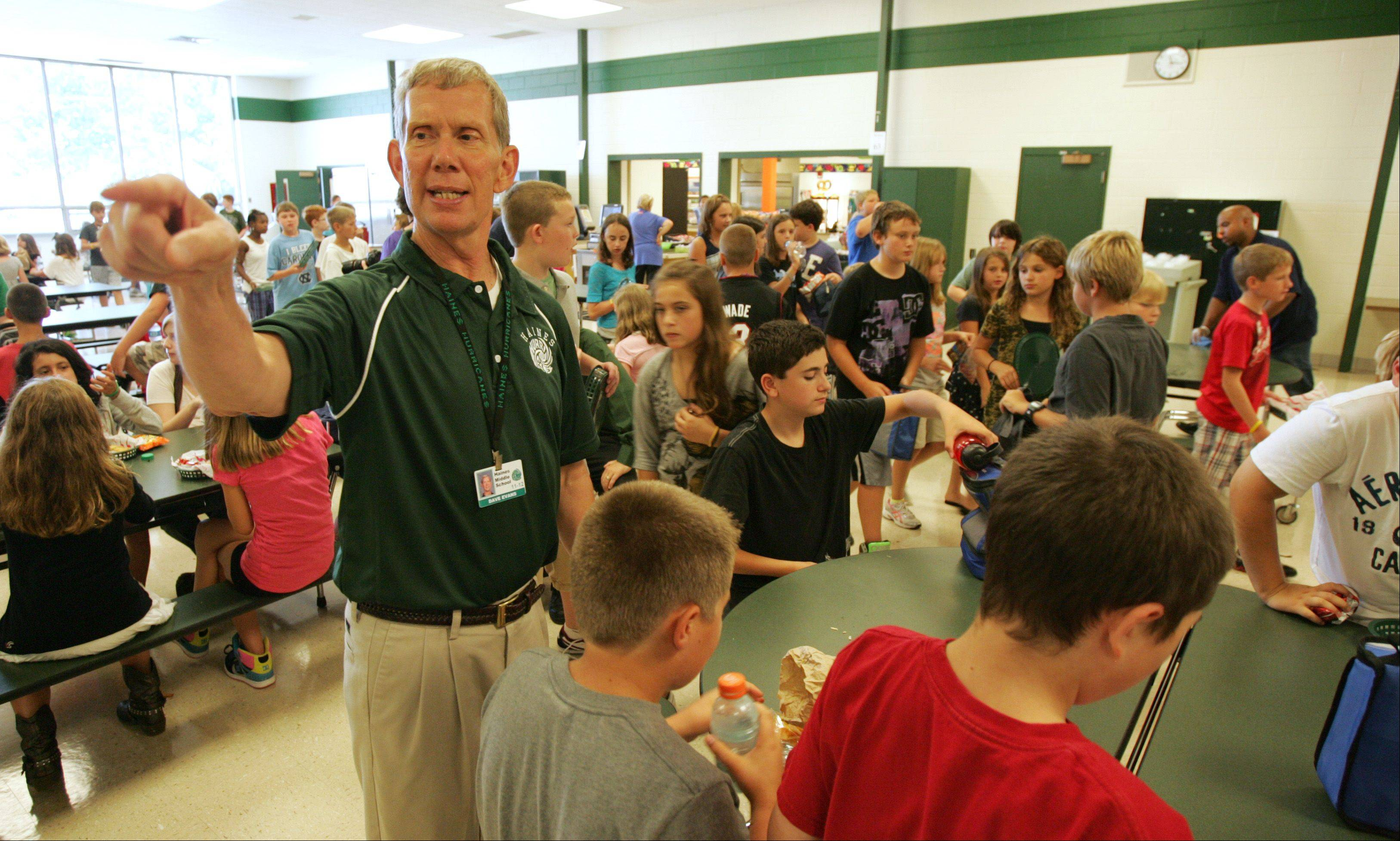 Social studies teacher Dave Evans tries to keep things organized as he dismisses students from the lunchroom Wednesday morning at Haines Middle School in St. Charles.