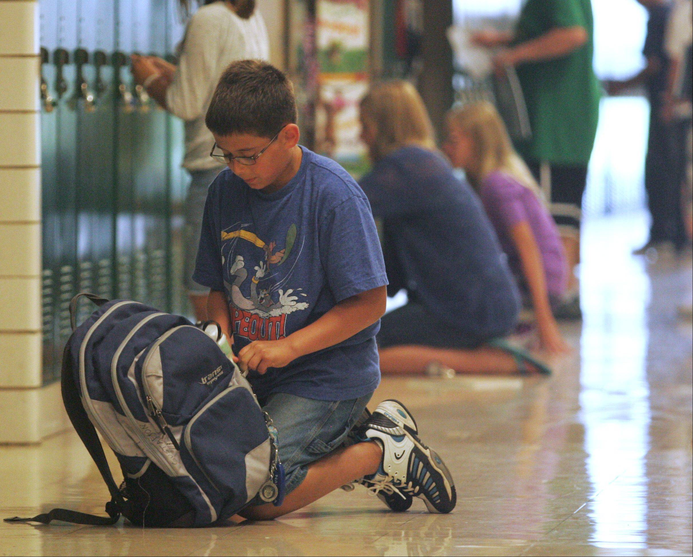 Sixth grader Ajay Gustafson puts some of his school supplies into his backpack between classes Wednesday morning at Haines Middle School in St. Charles.