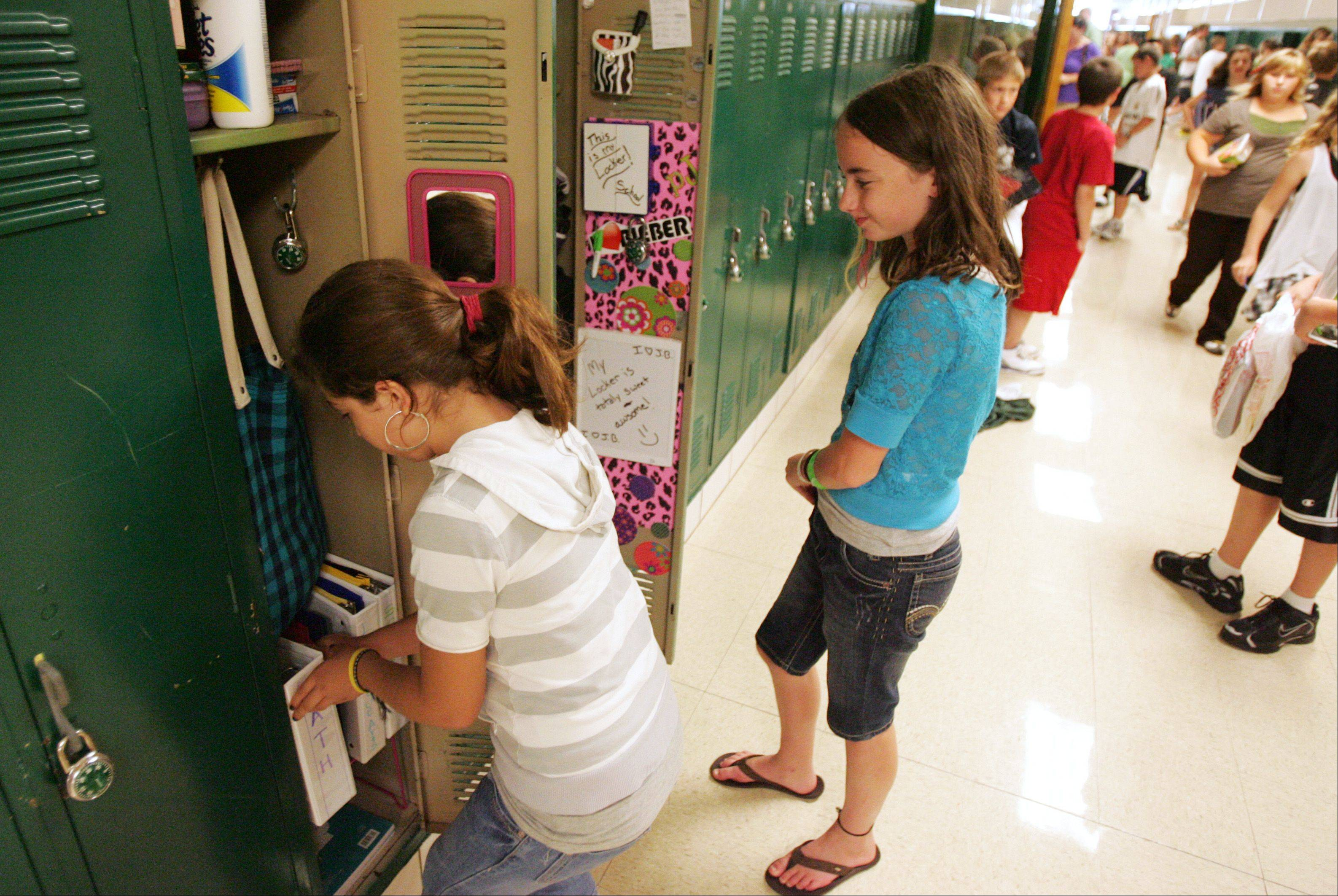 Sixth-grade students Ahtziri Orozco, left, and Paige Norkus get the hang of dealing with their lockers Wednesday morning at Haines Middle School in St. Charles.