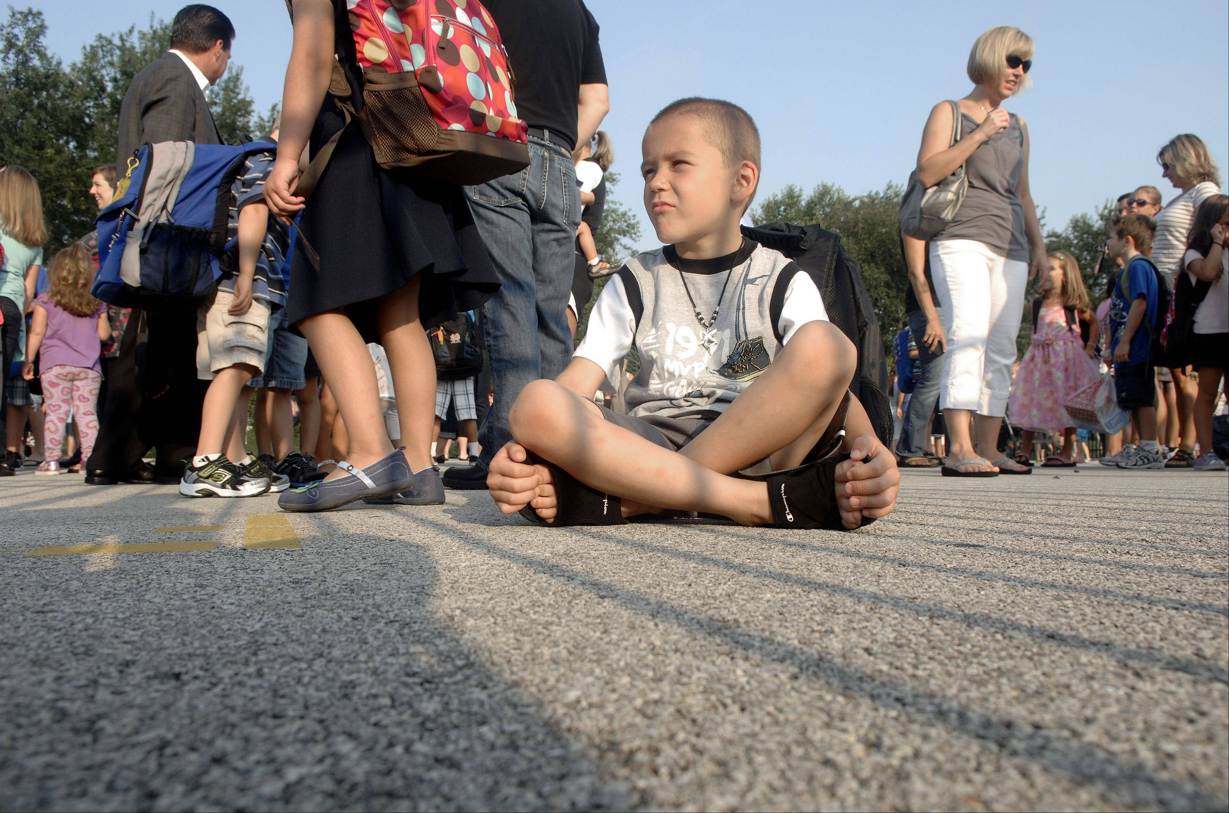 First grader Anthony Salazar patiently sits in line on the playground waiting for the first day of school at Williamsburg Elementary to start on Wednesday.