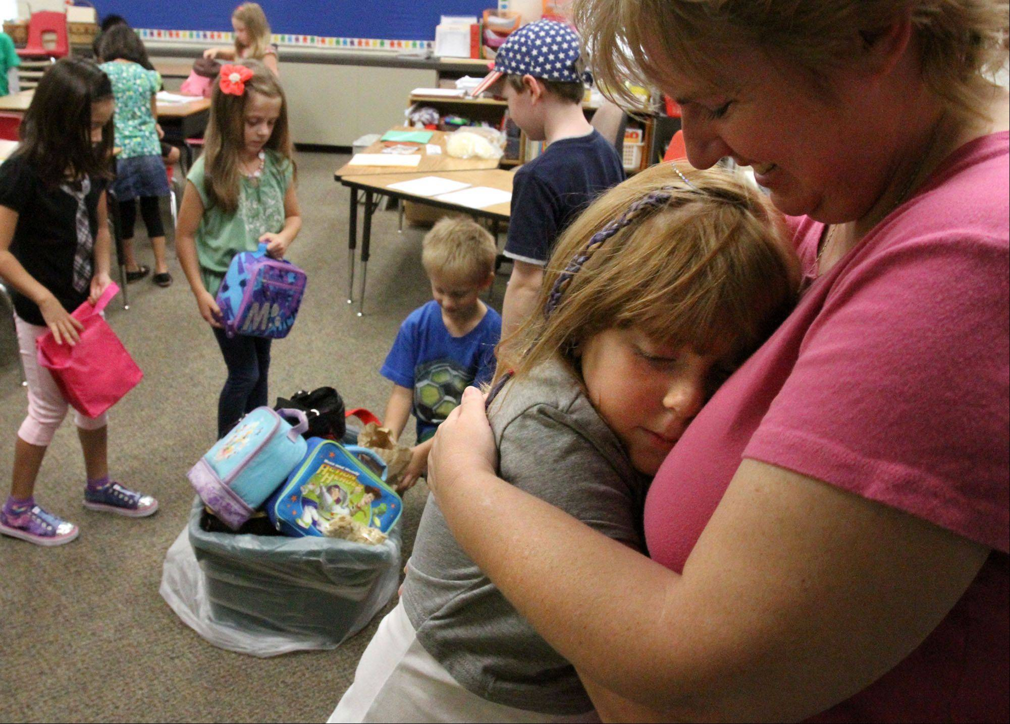 Crystal Engle gets a hug from her mom Loretta at the doorway to her second-grade class with Kristin Miller on the first day of school at Anne Fox School in Hanover Park on Wednesday.