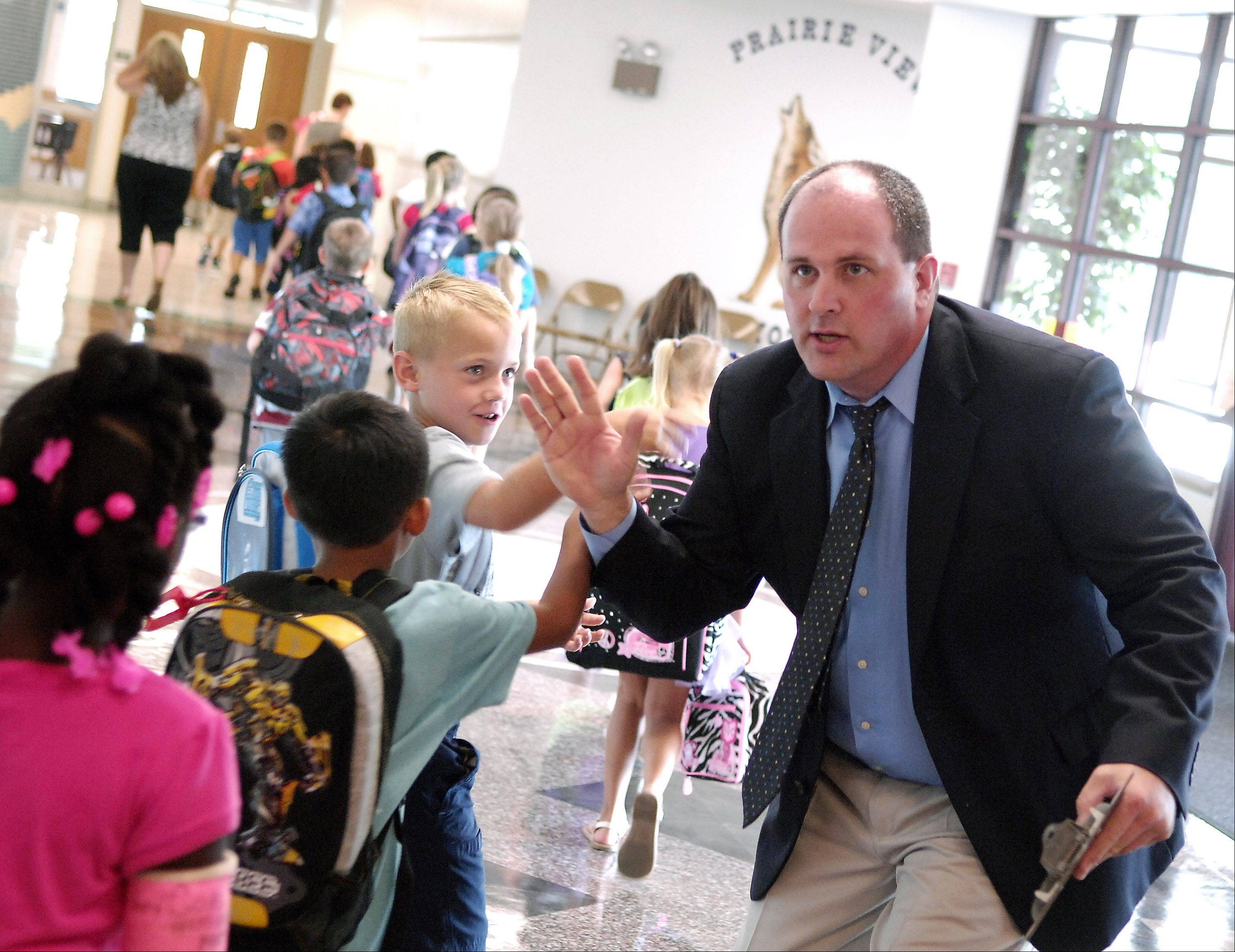 Prairie View Grade School Principal Dan Schuth high fives the students as they head to their classes during the first day of school for kids in Burlington Central District 301 Wednesday.