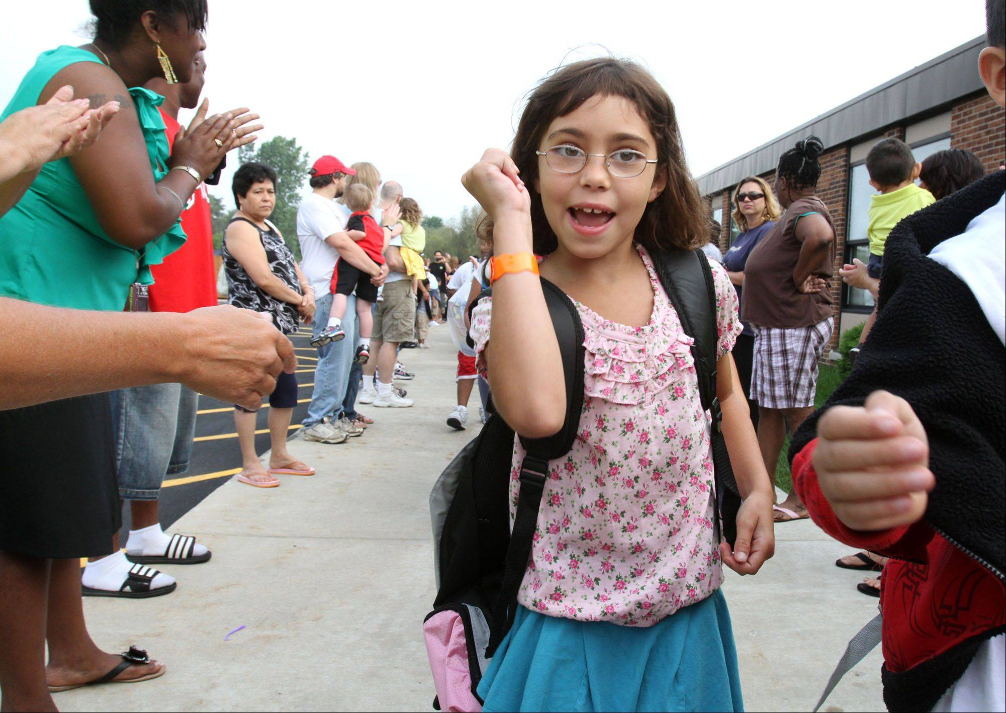 Third grader Arlene Benhart is happy to be returning to Anne Fox School as she walks through a Tunnel of Hope made up of staff, teachers, parents and community members lining the sidewalk outside the school's main entrance in Hanover Park on Wednesday, the first day of school in Schaumburg Township Elementary District 54.