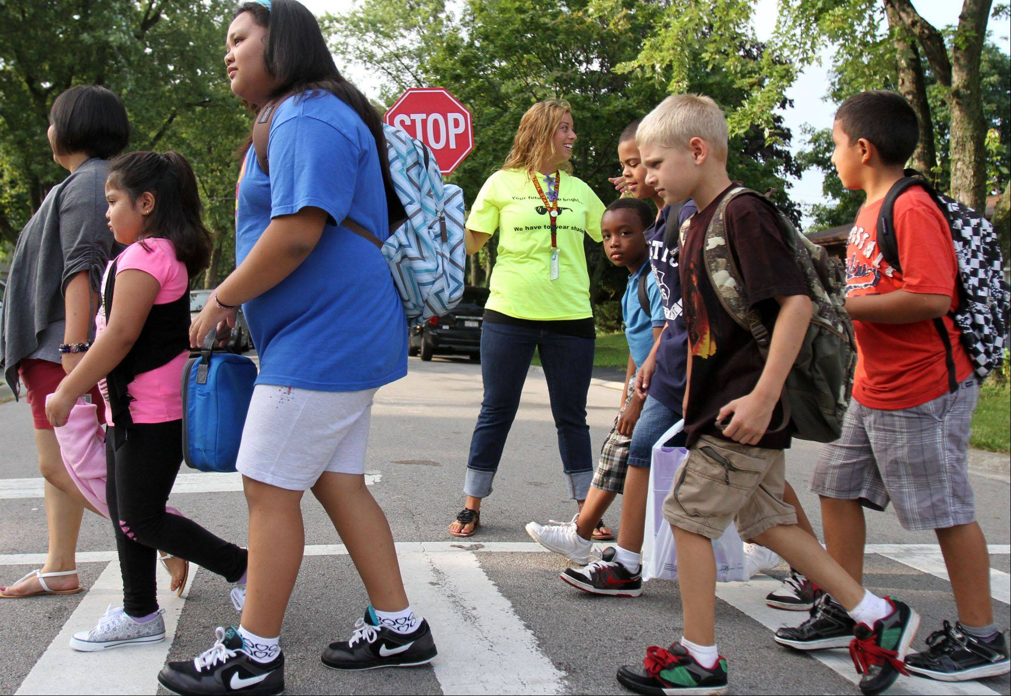 Speech teacher Amanda Kaiz helps students crossing the street to Anne Fox School on the first day of school in Hanover Park on Wednesday.