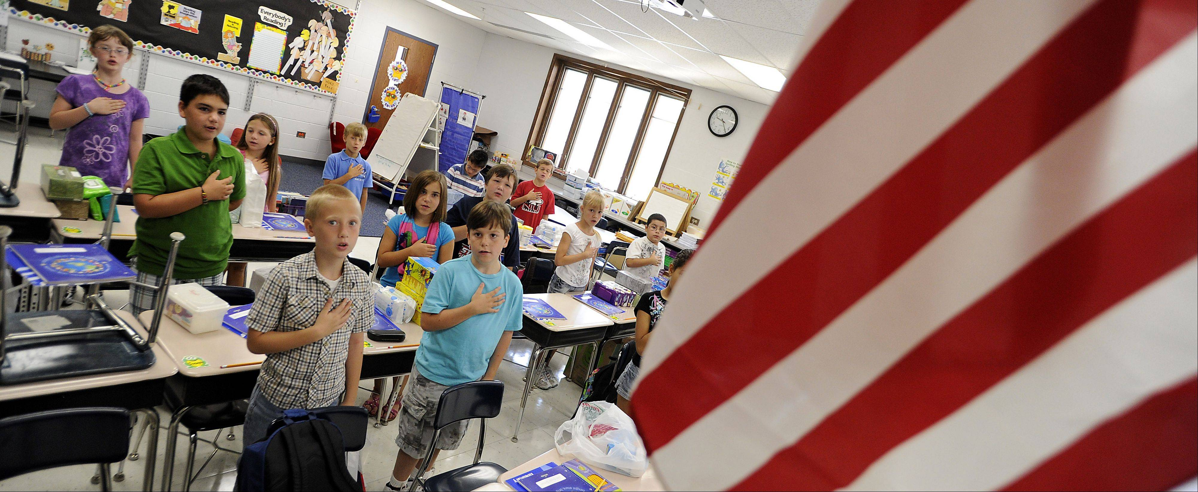 The classroom of 3rd grade teacher Mrs. Roi Petrides says the Pledge of Allegiance to start the day at Salt Creek Elementary school in Elk Grove Village on Wednesday.