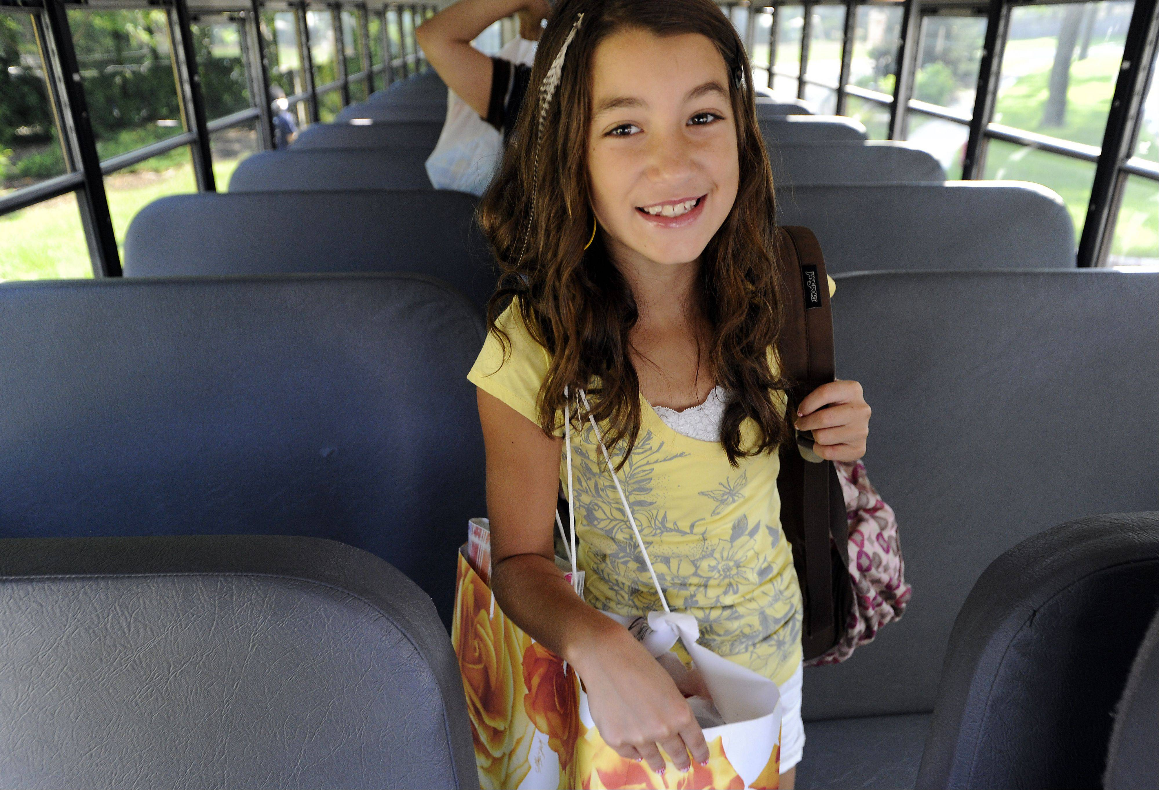 Julia Parisi, 10, in the 5th grade at Salt Creek Elementary School in Elk Grove Village exits her school bus loaded with gear excited about the new year.
