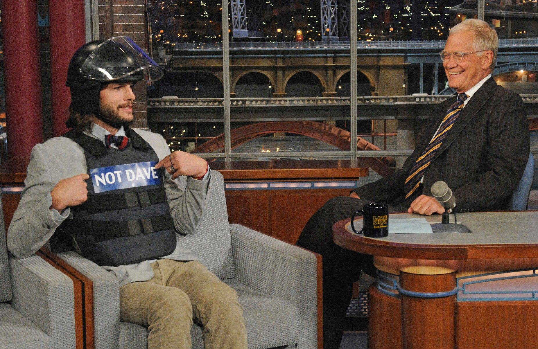 """Two and a Half Men"" star Ashton Kutcher, left, pokes fun at host David Letterman by wearing a helmet and bullet proof vest labeled ""Not Dave,"" on the set of the ""Late Show with David Letterman"" Wednesday."