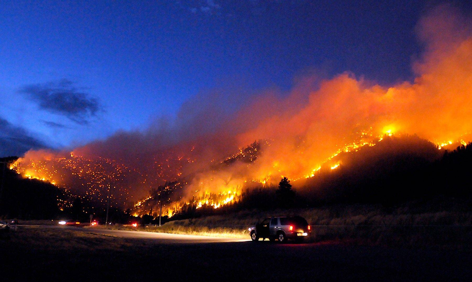 Flames light up the evening sky near Missoula, Mont., as a wildfire burns through timber. The fire spread quickly up the mountainside, and there were no reports of structures damaged or injuries.