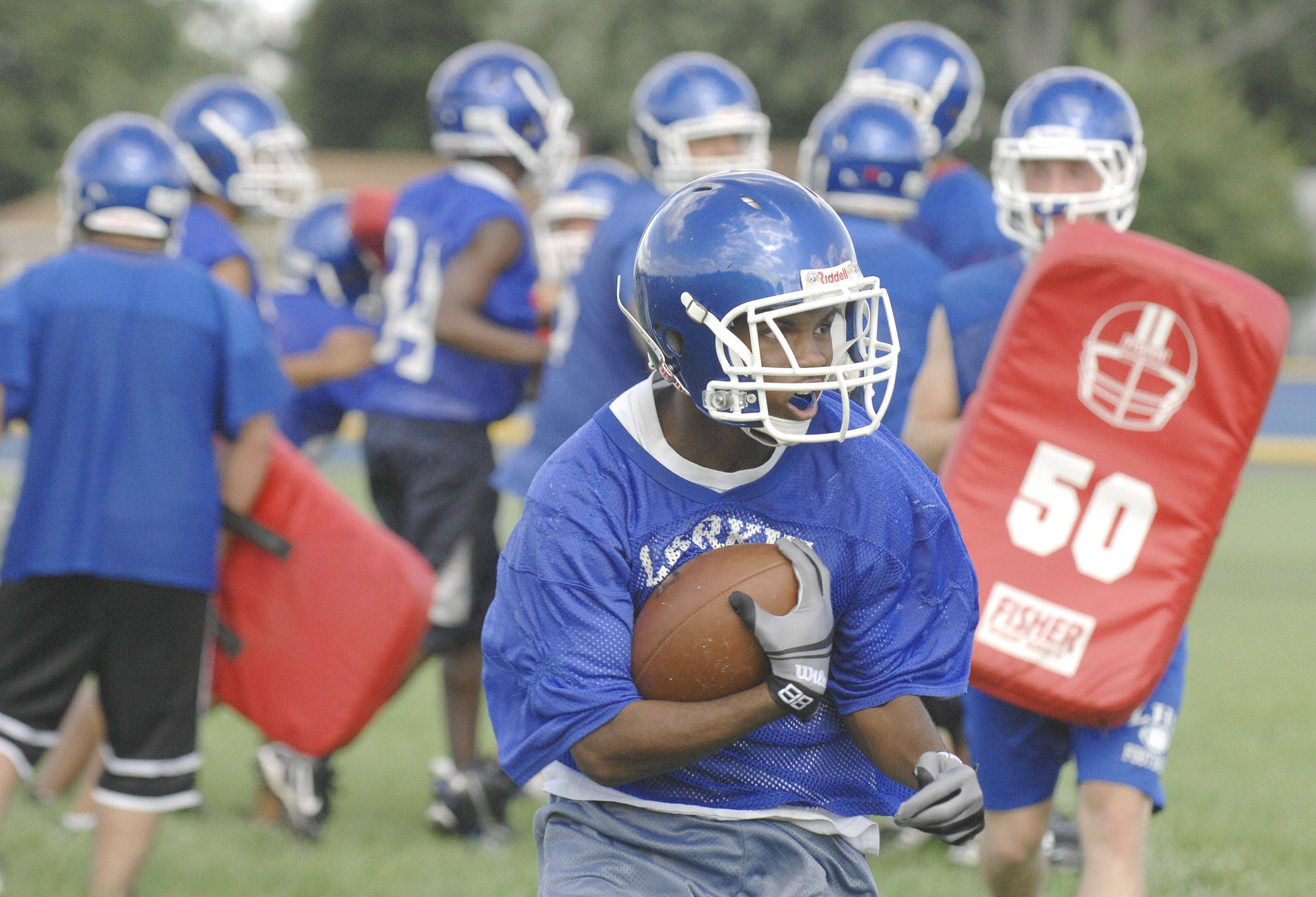 Keiren McKenzie dodges the defense in a drill during Larkin High School's varsity football practice on Wednesday, August 10.