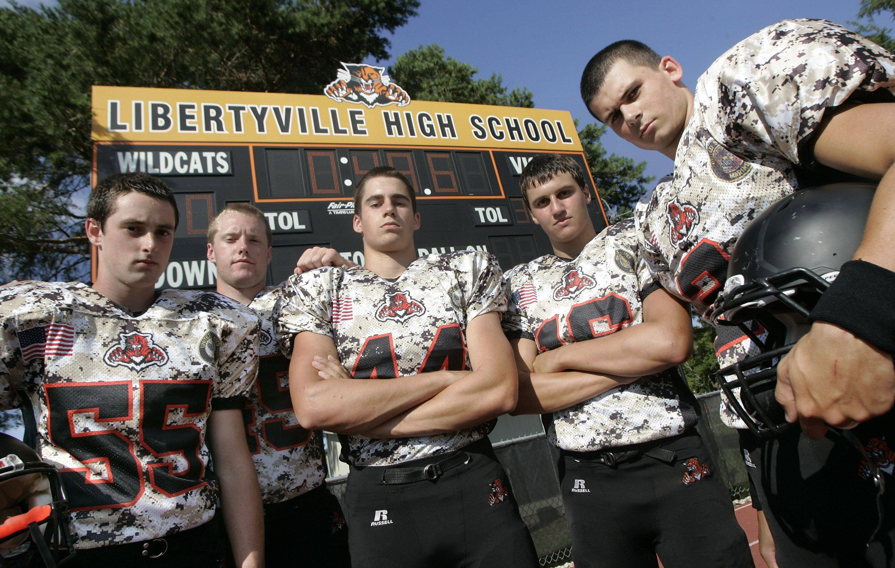 Alex Gough, left, Luke Mathewson, Michael Parker, Steve Skul and Sam Styler model the camouflage jerseys they'll be wearing in the season opener tonight against visiting Barrington.