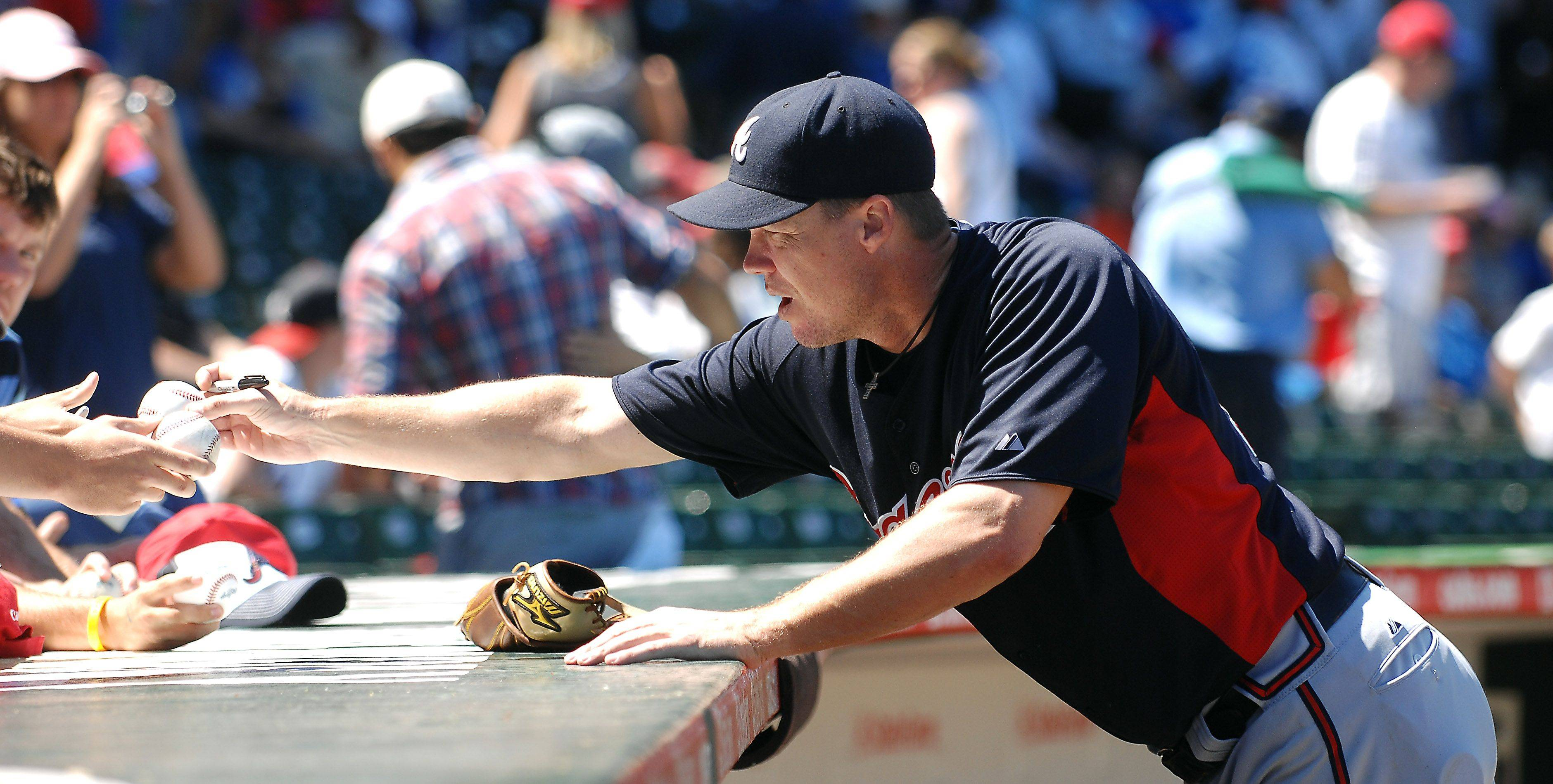 Atlanta Braves third baseman Chipper Jones signs autographs before Thursday's game at Wrigley Field in Chicago.