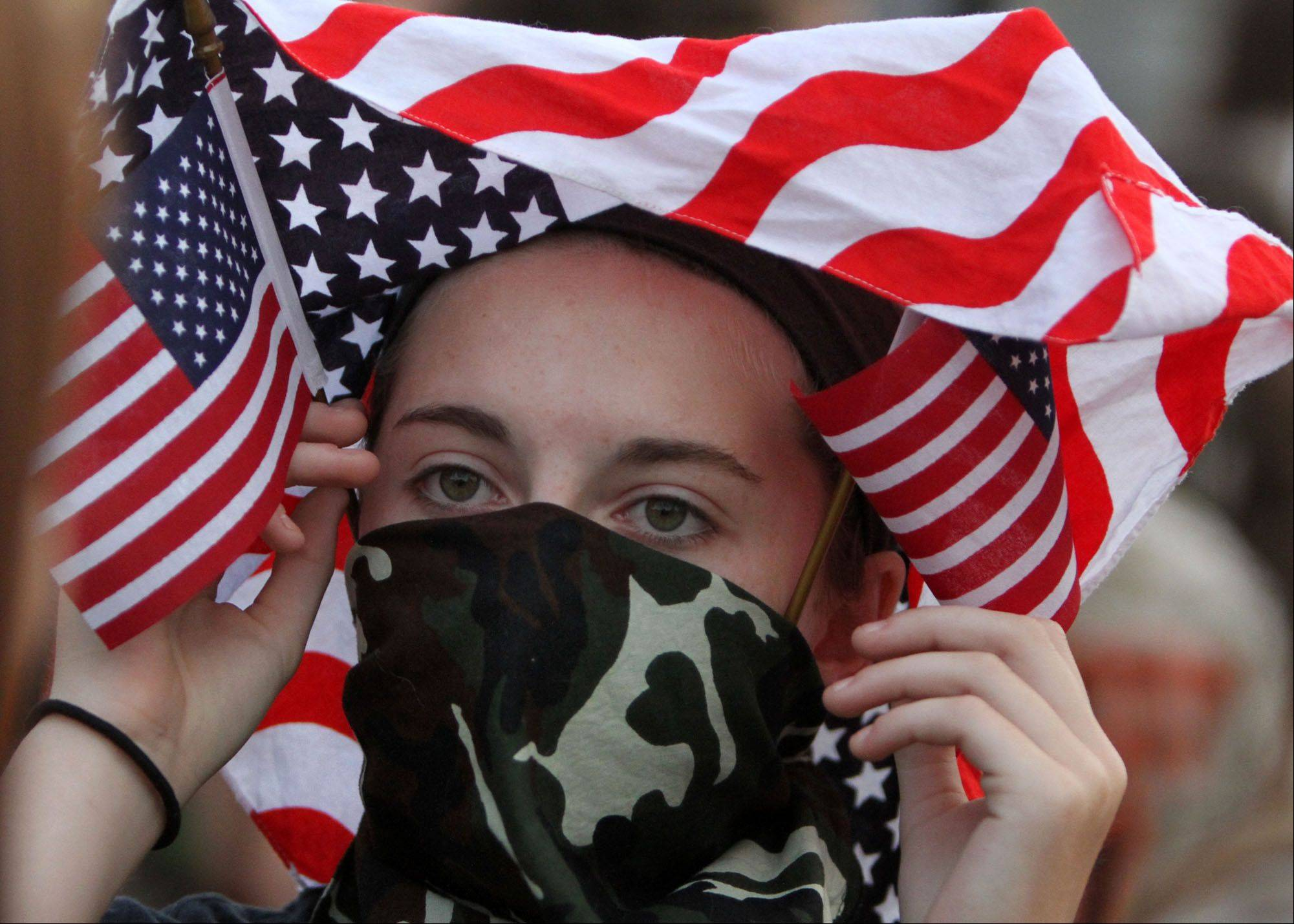 Libertyville sophomore Sydney Mudd wears a military camouflage mask and donning an American Flag for military appreciation night as Libertyville battles Barrington at Libertyville on Friday, August 26th.