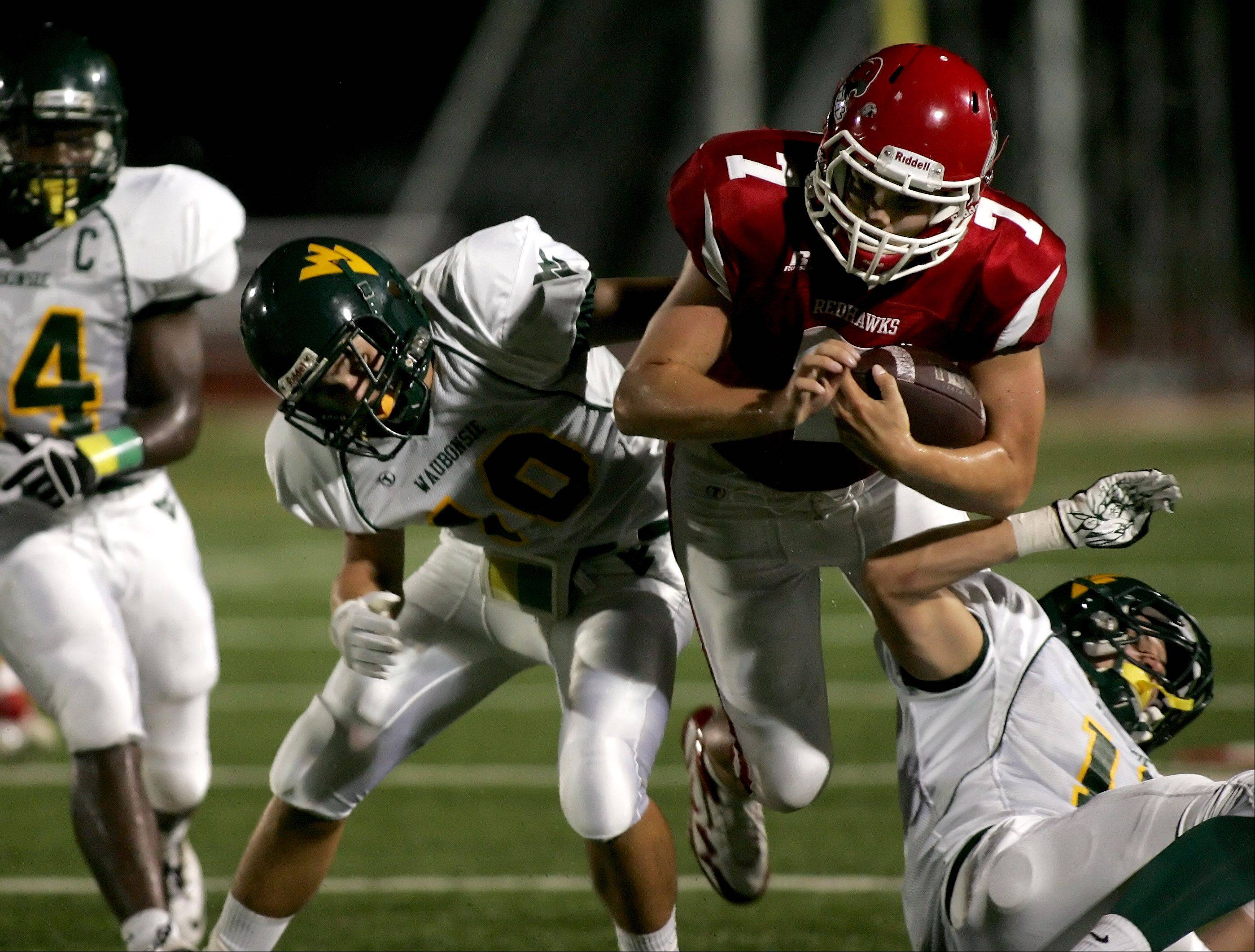 Week 1- Connor Mersch, left and Jim Delaney, right, of Waubonsie Valley tackle quarterback Ian Lewandowski of Naperville Central.