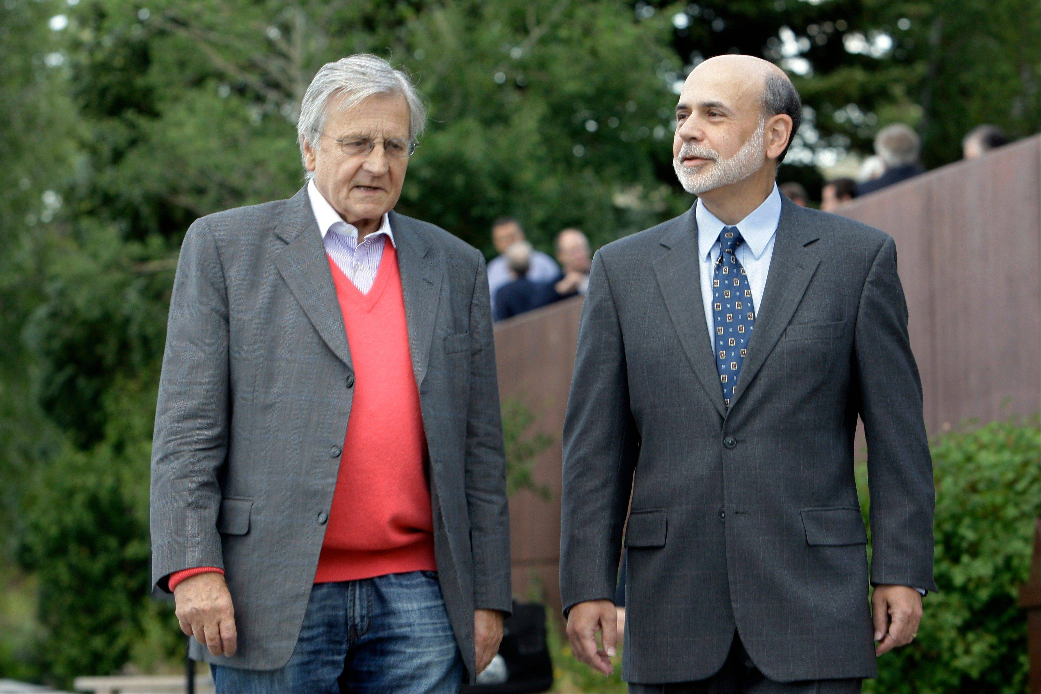 Federal Reserve chairman Paul Bernanke, right, and Jean-Claude Trichet, of France, president of the European Central Bank, take a morning stroll on the veranda of the Jackson Lake Lodge, before the morning session of the Economic Policy Symposium at Jackson Hole in Moran, Wyo., Friday.