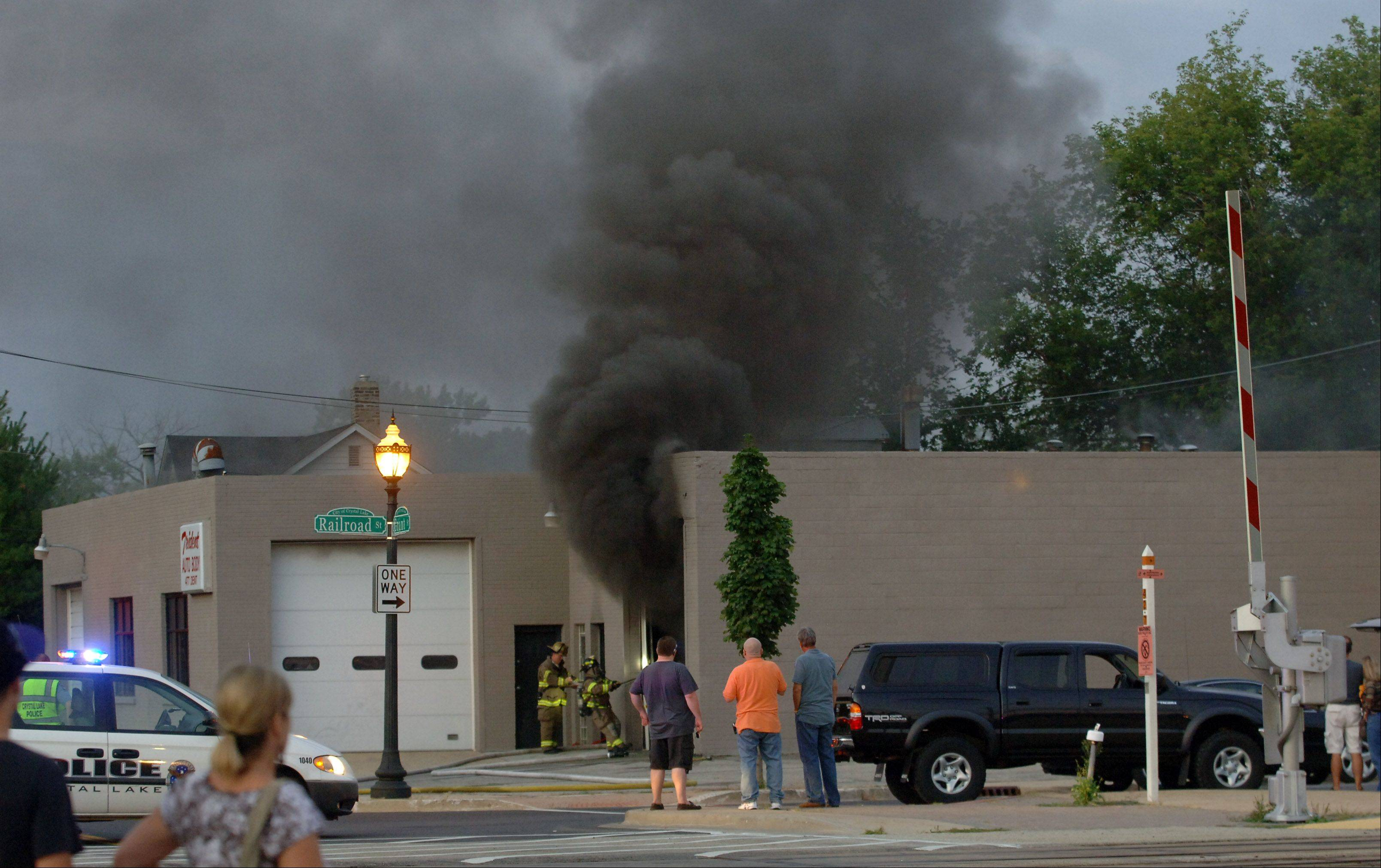Crystal Lake firefighters battle a fire at the Trident Auto Body shop at 80 Railroad St. in downtown Crystal Lake Friday. Fire officials were notified of the fire around 7:30 p.m. and arrived to find heavy black smoke pouring out of the roof and doors.