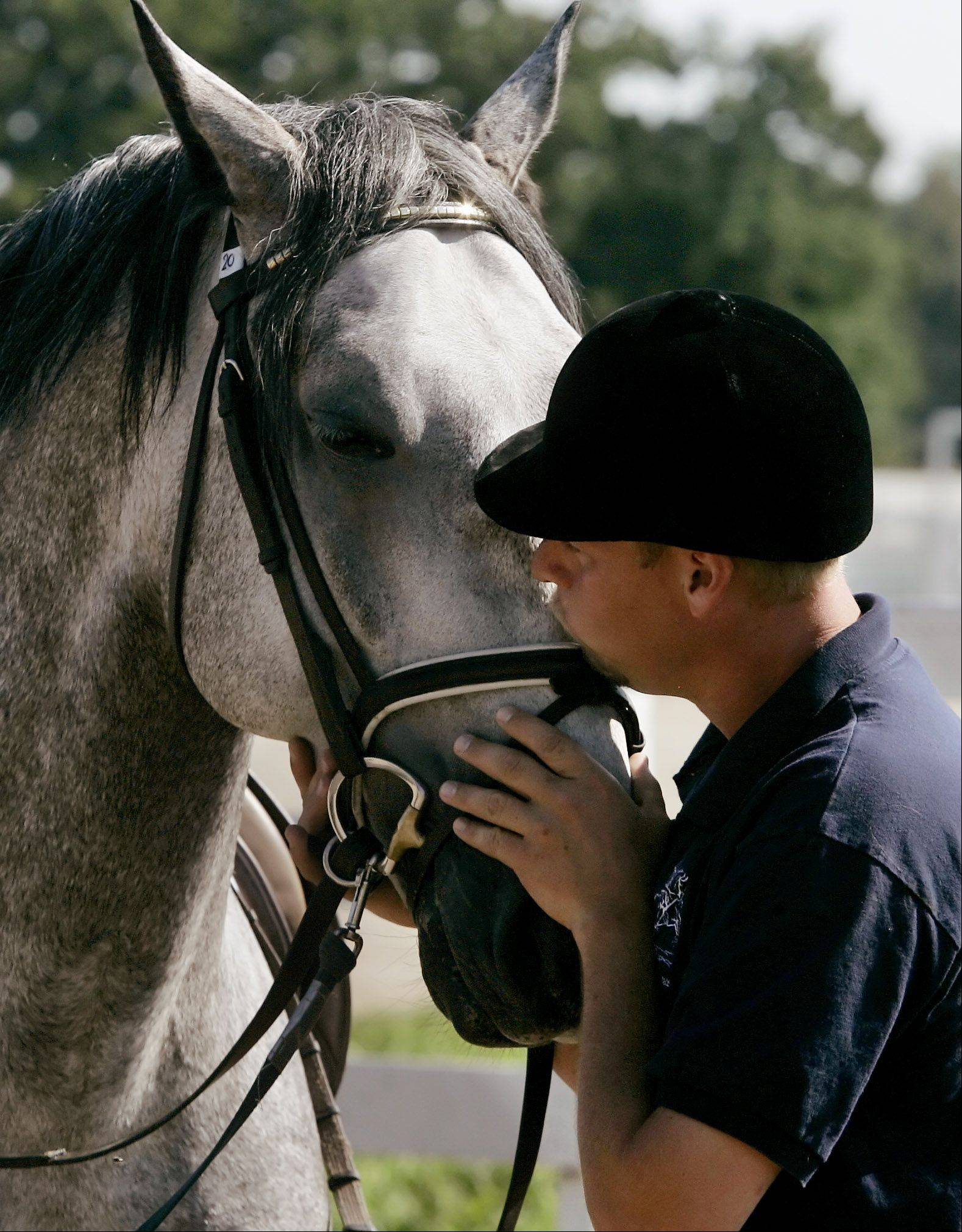 Dressage trainer Victor Pozzo gives Favory VII Anita a kiss after riding him in the training ring at Tempel Farms.