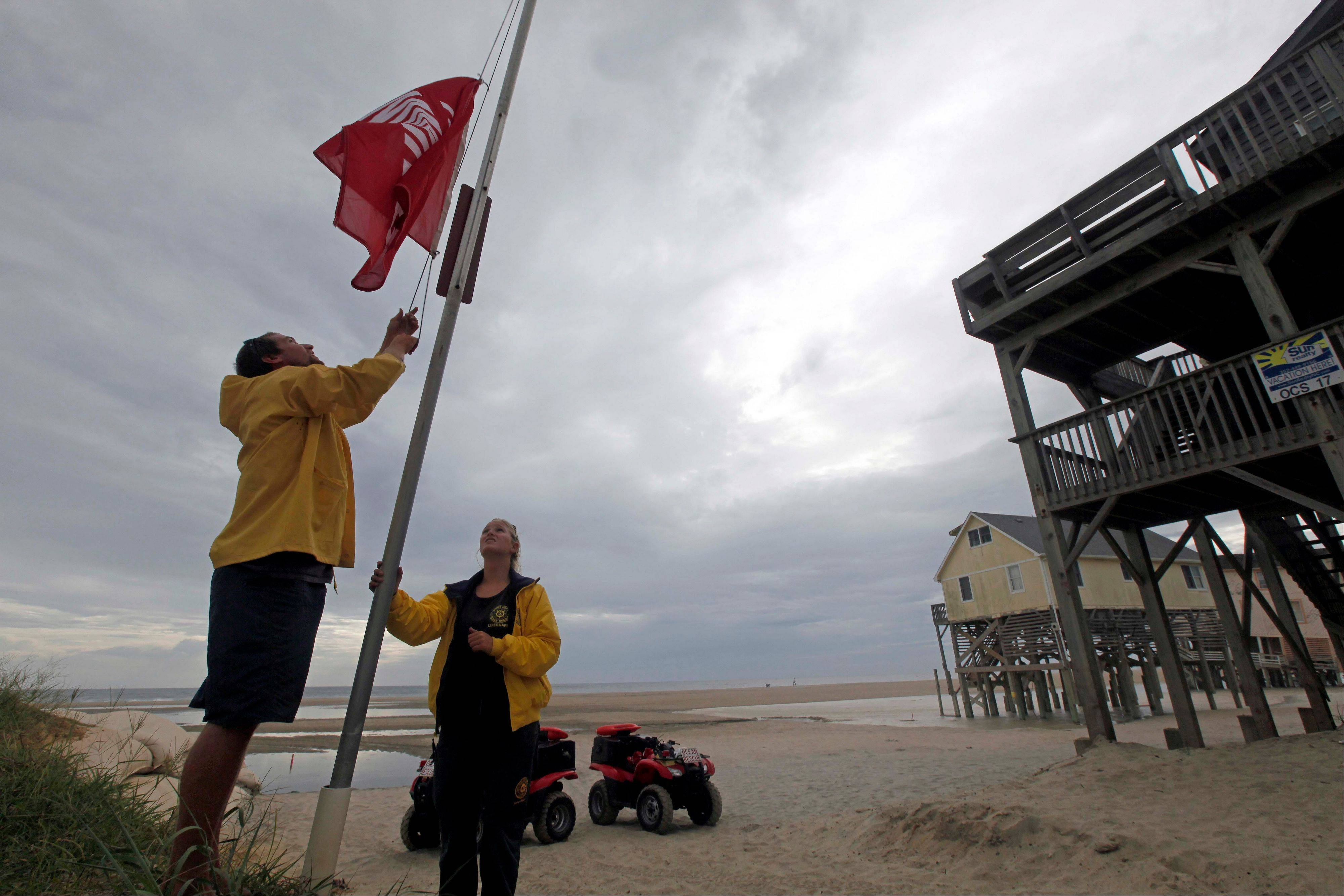Nags Head Ocean Rescue lifeguards Ben Mechak, left, an Erika Audfroid hoist a no swimming flag in Nags Head, N.C., Friday, Aug. 26, 2011 as Hurricane Irene takes aim at the North Carolina coast. The full force of Hurricane Irene was still a day away from the East Coast but heightened waves began hitting North Carolina's Outer Banks early Friday.
