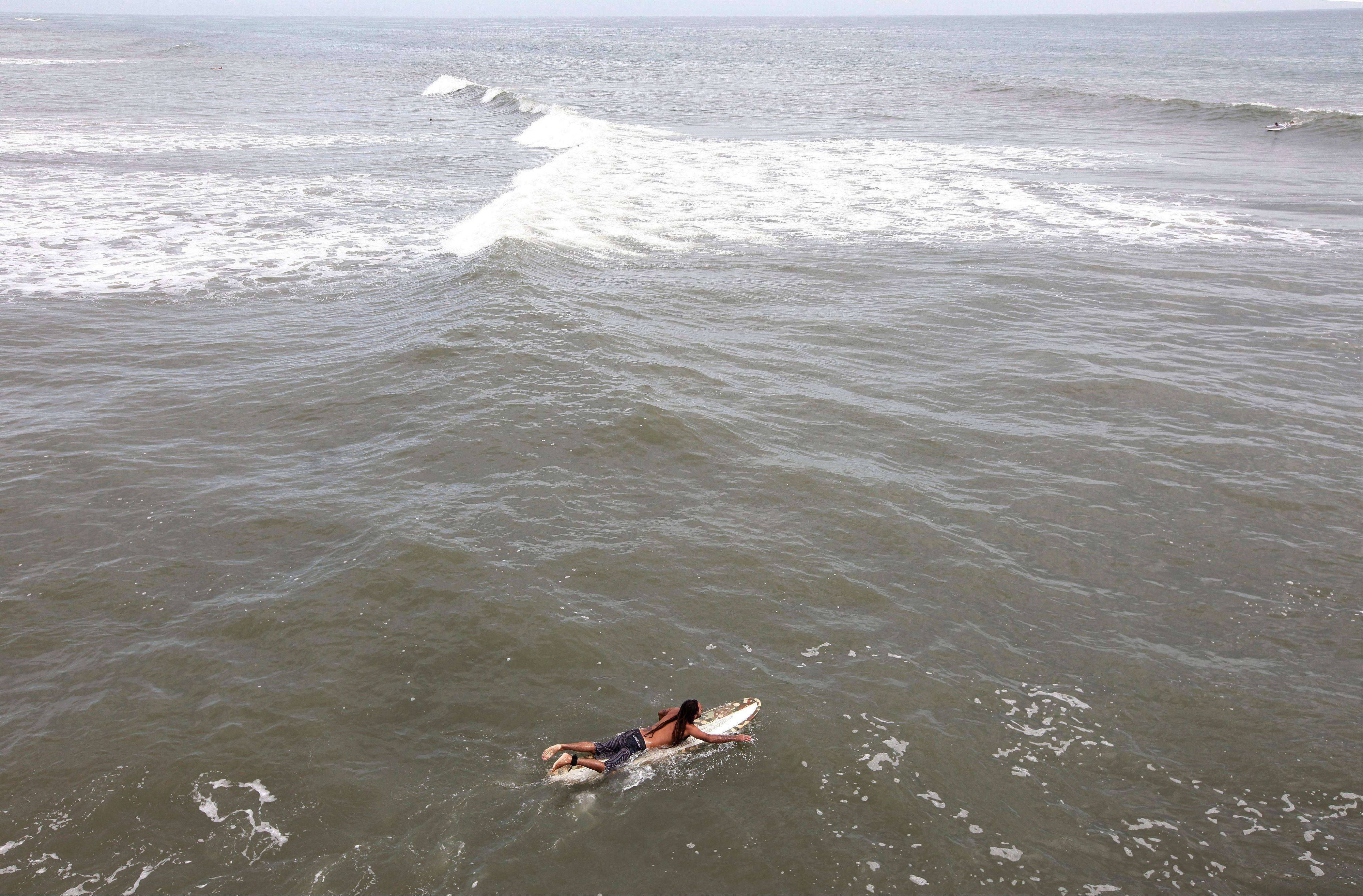 A surfer paddles out hoping to catch some big waves ahead of the arrival of Hurricane Irene in Nags Head, N.C., Friday, Aug. 26, 2011 on North Carolina's Outer Banks.