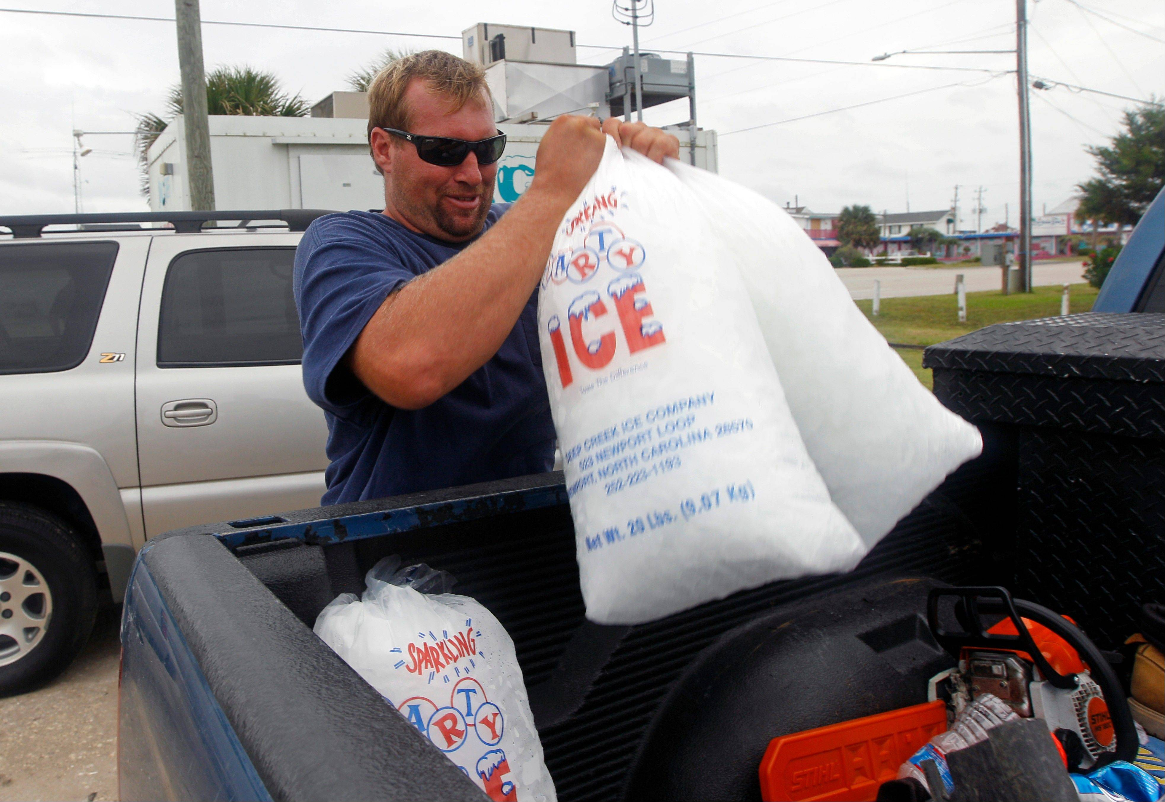 Mike Small, of Morehead City, N.C., loads bags of ice into his truck in Atlantic Beach, N.C., Friday, Aug. 26, 2011 as Hurricane Irene heads toward the North Carolina coast. Hurricane warnings remained in effect from North Carolina to New Jersey. Hurricane watches were in effect even farther north and included Long Island, Martha's Vineyard and Nantucket, Mass.