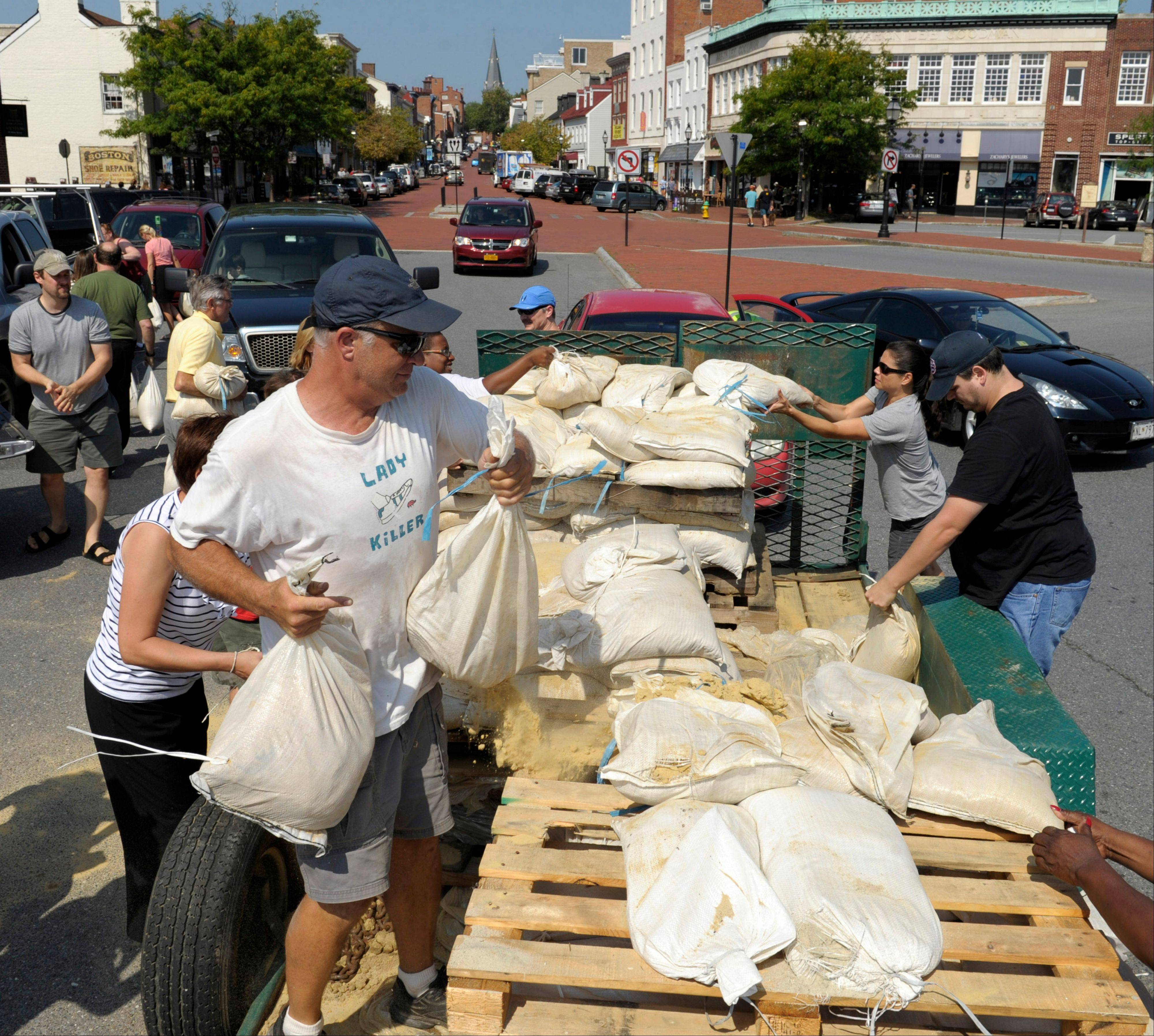 People take sandbags off a truck as residents prepare for Hurricane Irene in Annapolis, Md., Friday, Aug. 26, 2011.