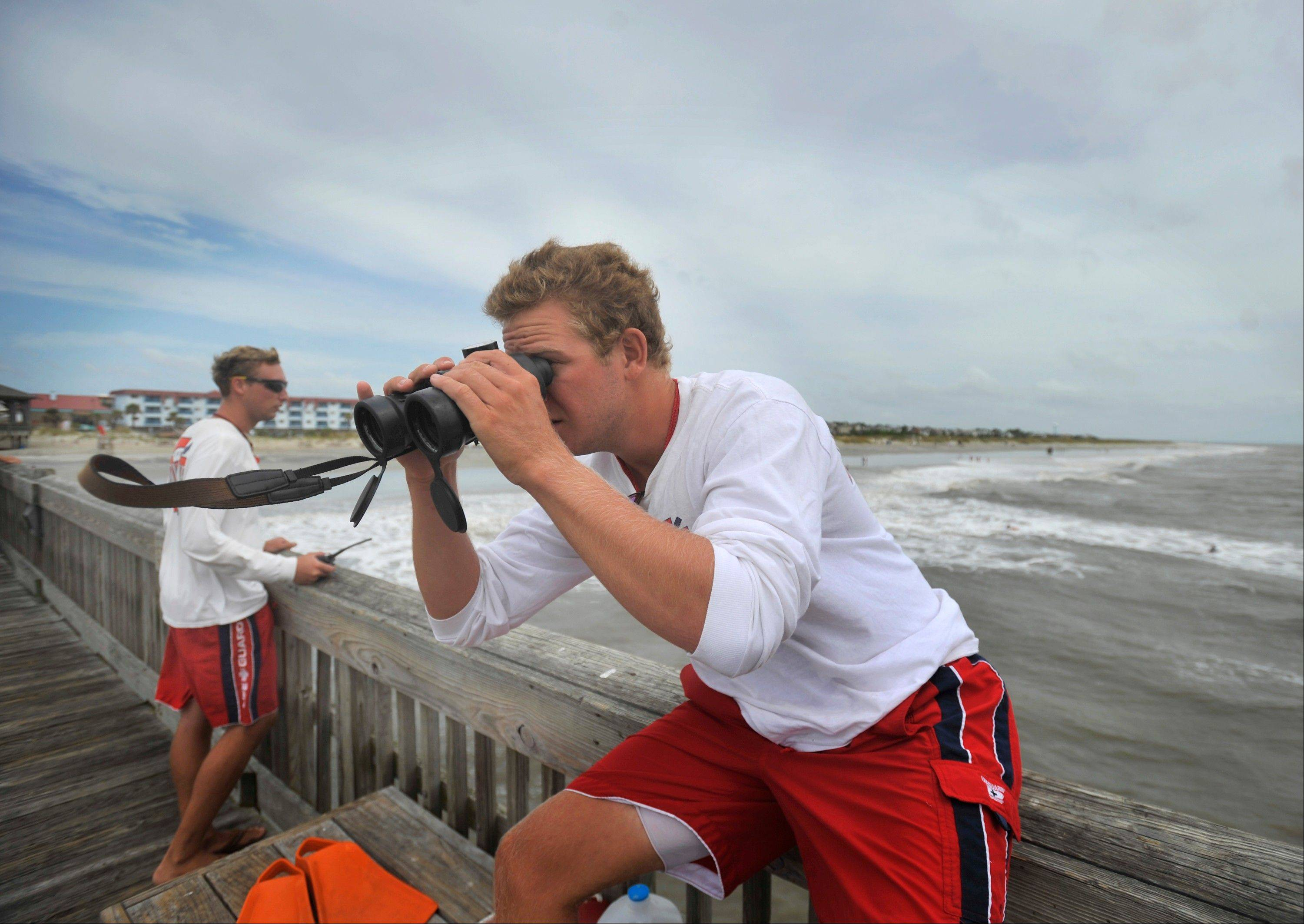 Tybee Island Ocean Rescue lifeguard Andrew Robinson watches surfers with a pair of binoculars after closing the water to swimmers from on the pier in Tybee Island, Ga., Friday, Aug. 26, 2011. Due to high waves and hazardous rip currents from the outer bands of Hurricane Irene, the lifeguards decided to close the water to swimmers. Surfers, kayakers and paddle boarders still brave the waves.