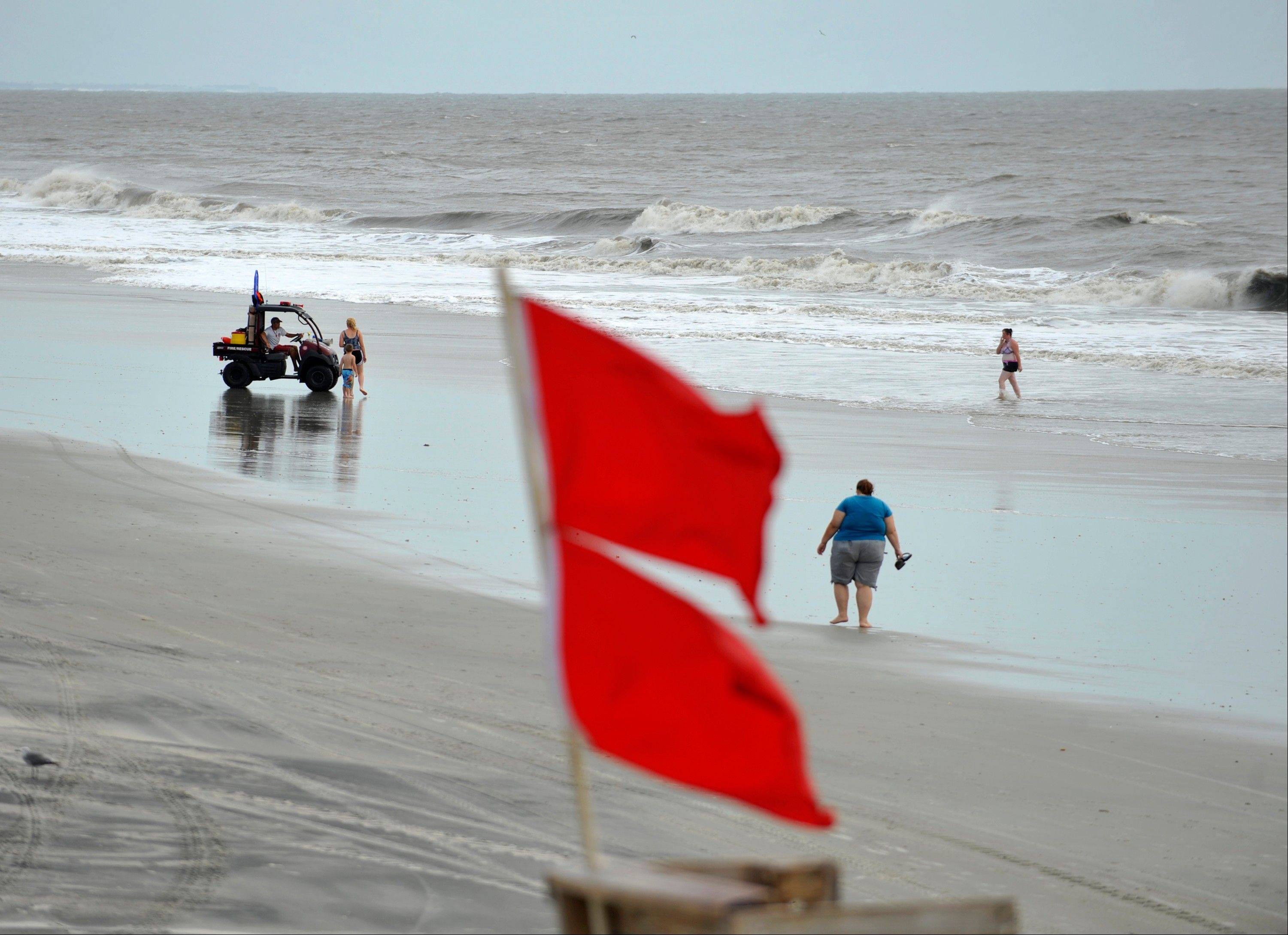 A member of the Tybee Island Ocean Rescue team closes the water to swimmers in Tybee Island, Ga., Friday, Aug. 26, 2011. Due to high waves and hazardous rip currents from the outer bands of Hurricane Irene, the lifeguards decided to close the water to swimmers. Surfers, kayakers and paddle boarders still brave the waves.