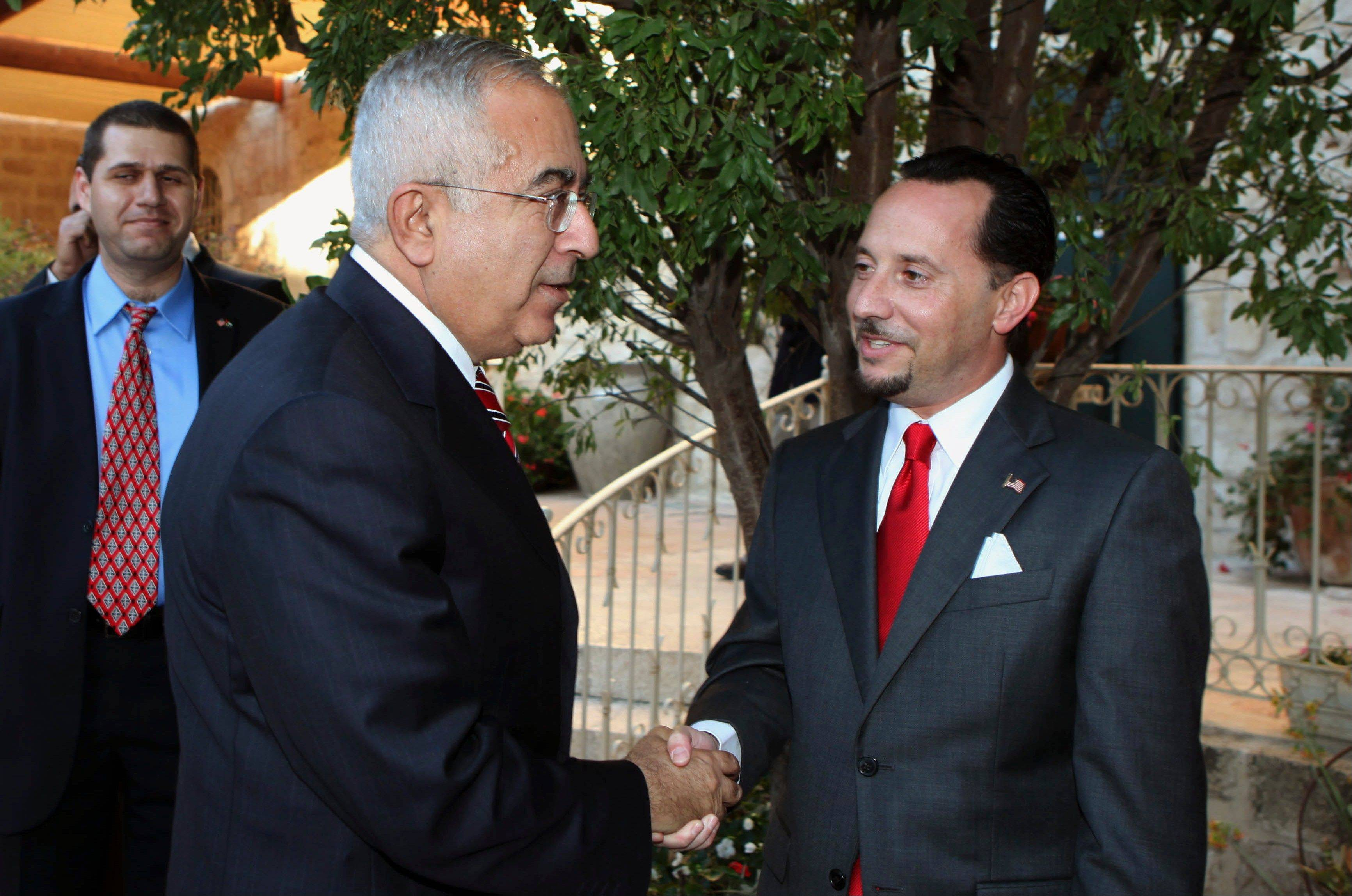 "In this Wednesday, June 30, 2010 file photo, U.S. Consul General of Jerusalem Daniel Rubinstein, right, shakes hands with Palestinian Prime Minister Salam Fayyad, during a reception ahead of July 4 U.S. Independence Day celebrations at the American Consulate in Jerusalem. Senior Palestinian official Saeb Erekat said the U.S. Consul General in Jerusalem, Daniel Rubinstein told him Friday that the U.S. will take ""punitive measures"" to stop financial support if the Palestinians proceed with seeking U.N. recognition of statehood in September."