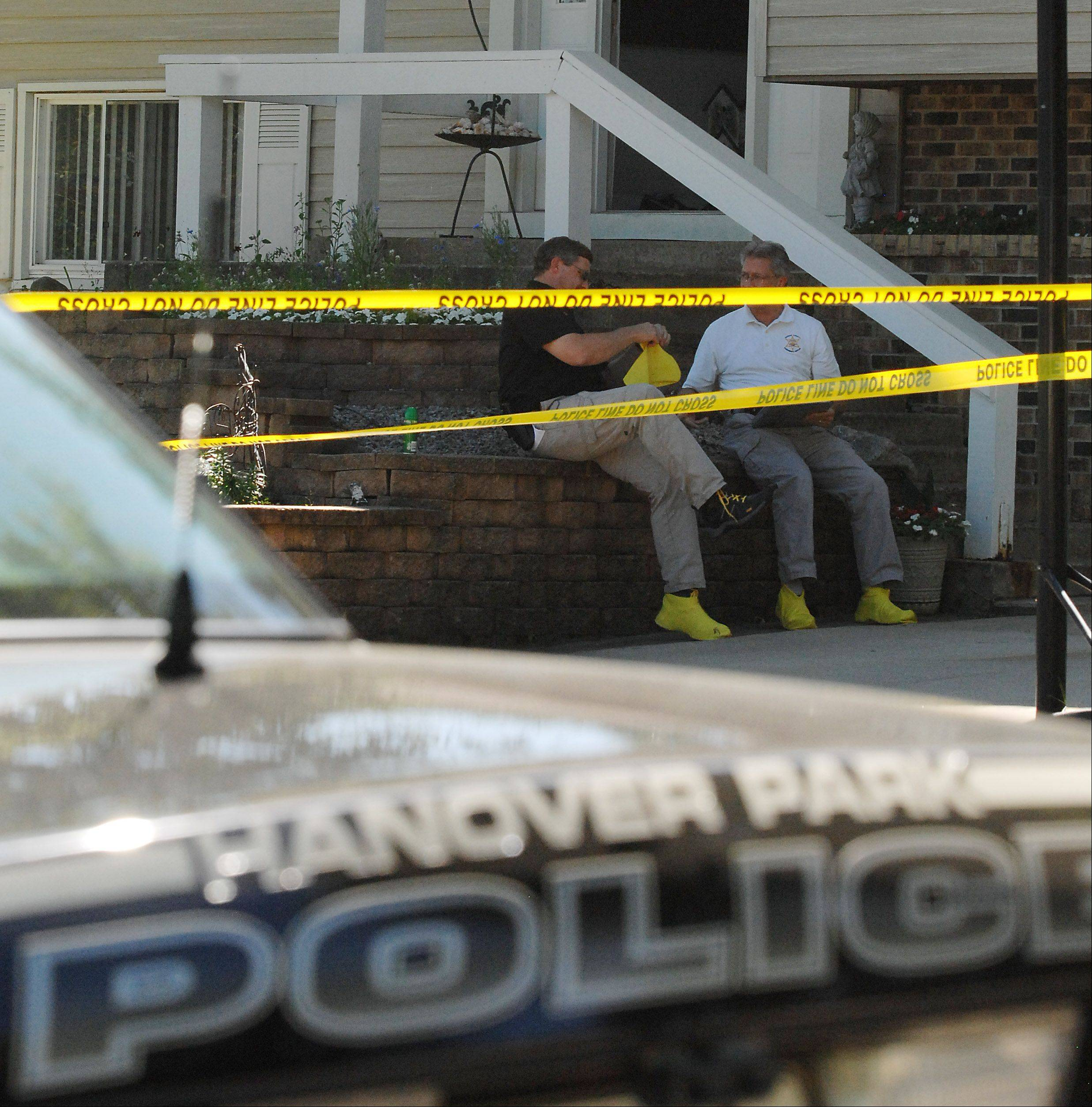 Hanover Park investigators put on crime scene bootees before entering a house on Barr Court, the scene of a murder on Thursday.