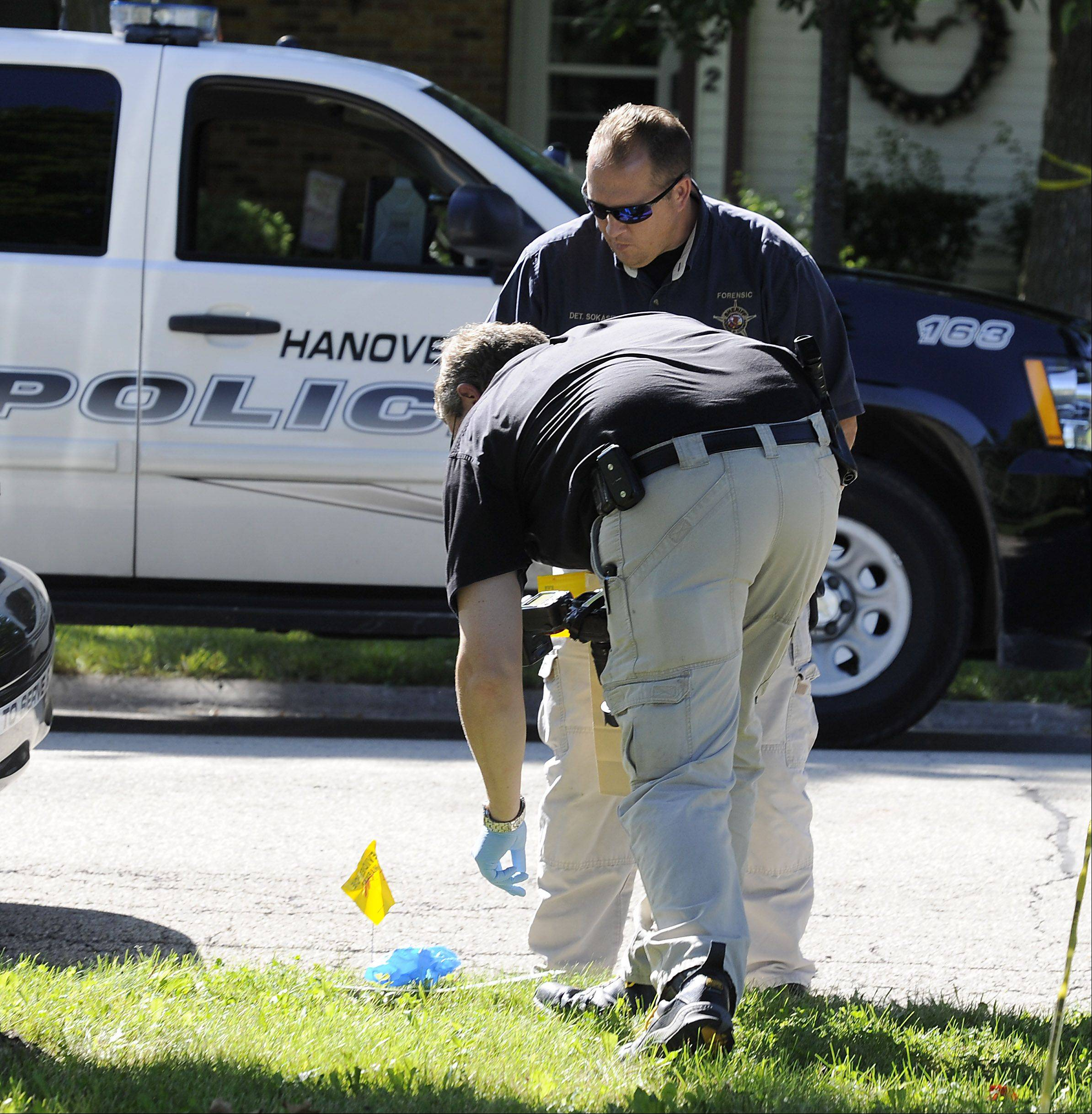 Hanover Park investigators mark evidence across the street from a murder in a house on Barr Court on Thursday.