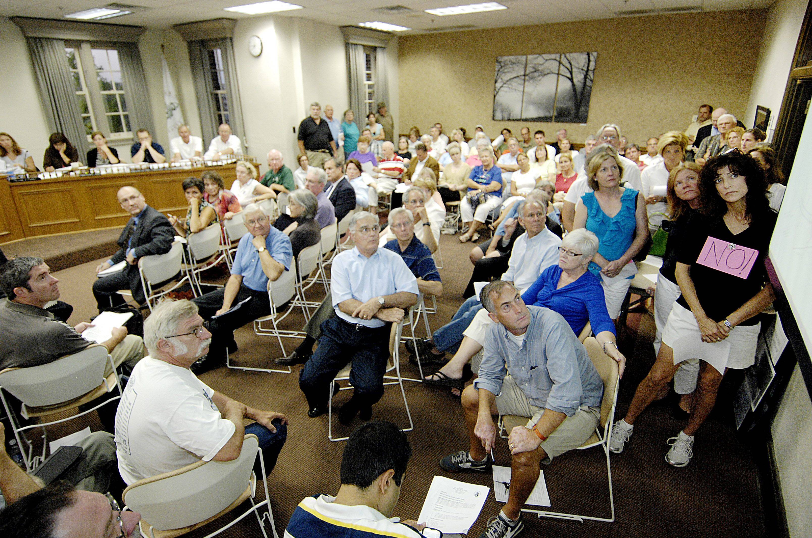 Concerned residents pack the Glen Ellyn village hall board room to watch Glenbard High School District 87 officials' presentation to the plan commission on the zoning variations for proposed lights at Memorial Field.