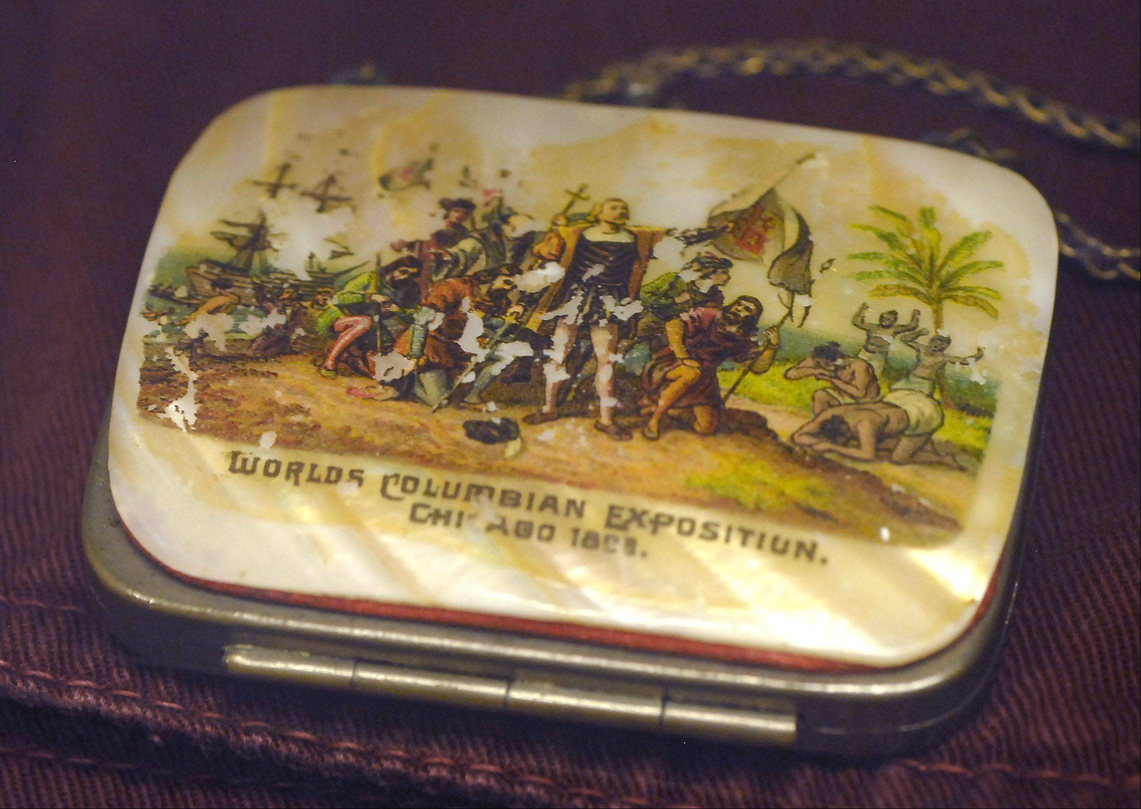 A small coin purse from the 1893 Columbian Exposition in Chicago features the landing of Columbus in the Americas.