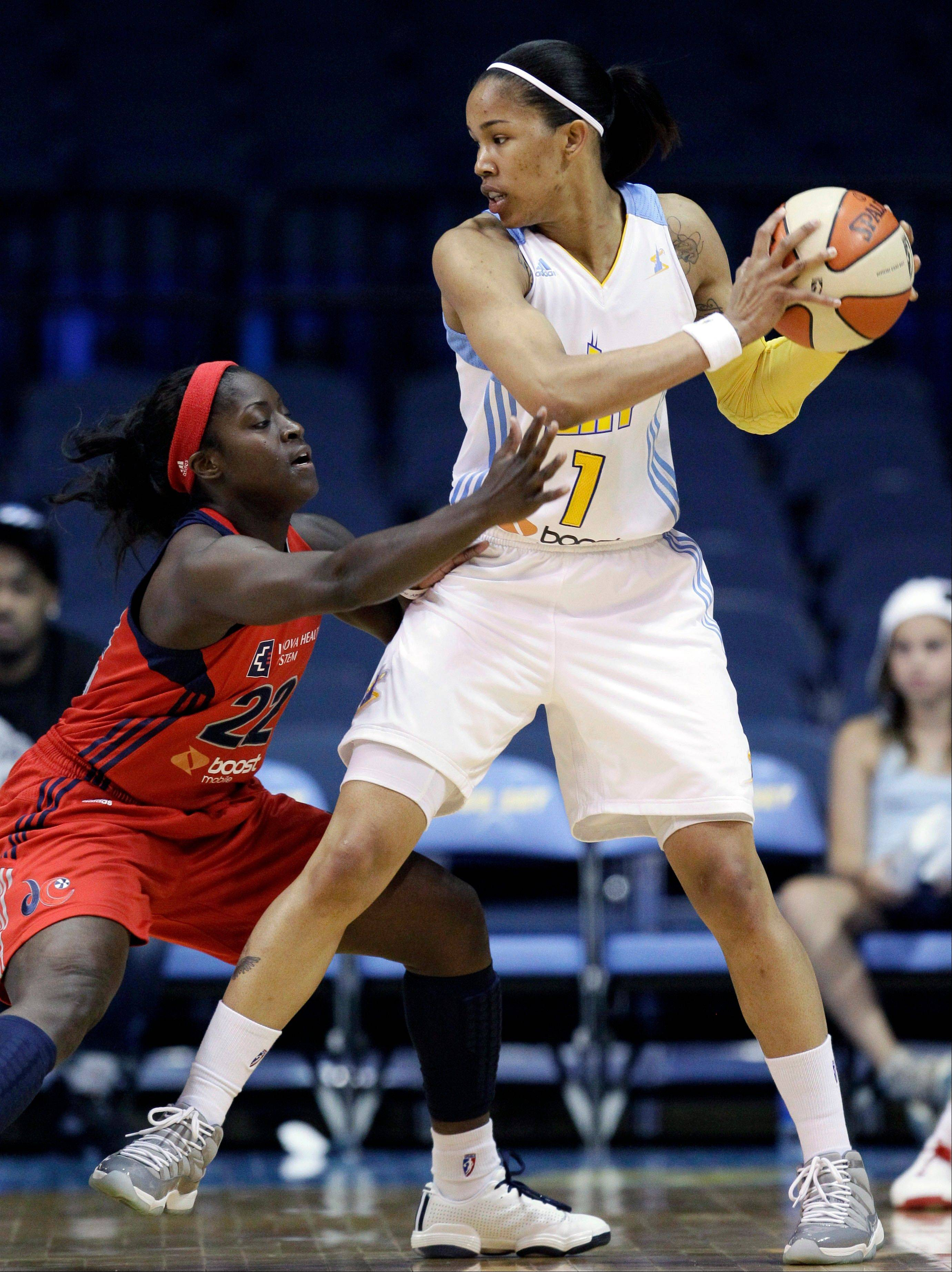 The Sky's Tamera Young looks to pass under defensive pressure from the Mystics' Matee Ajavon on Friday night at Allstate Arena in Rosemont.
