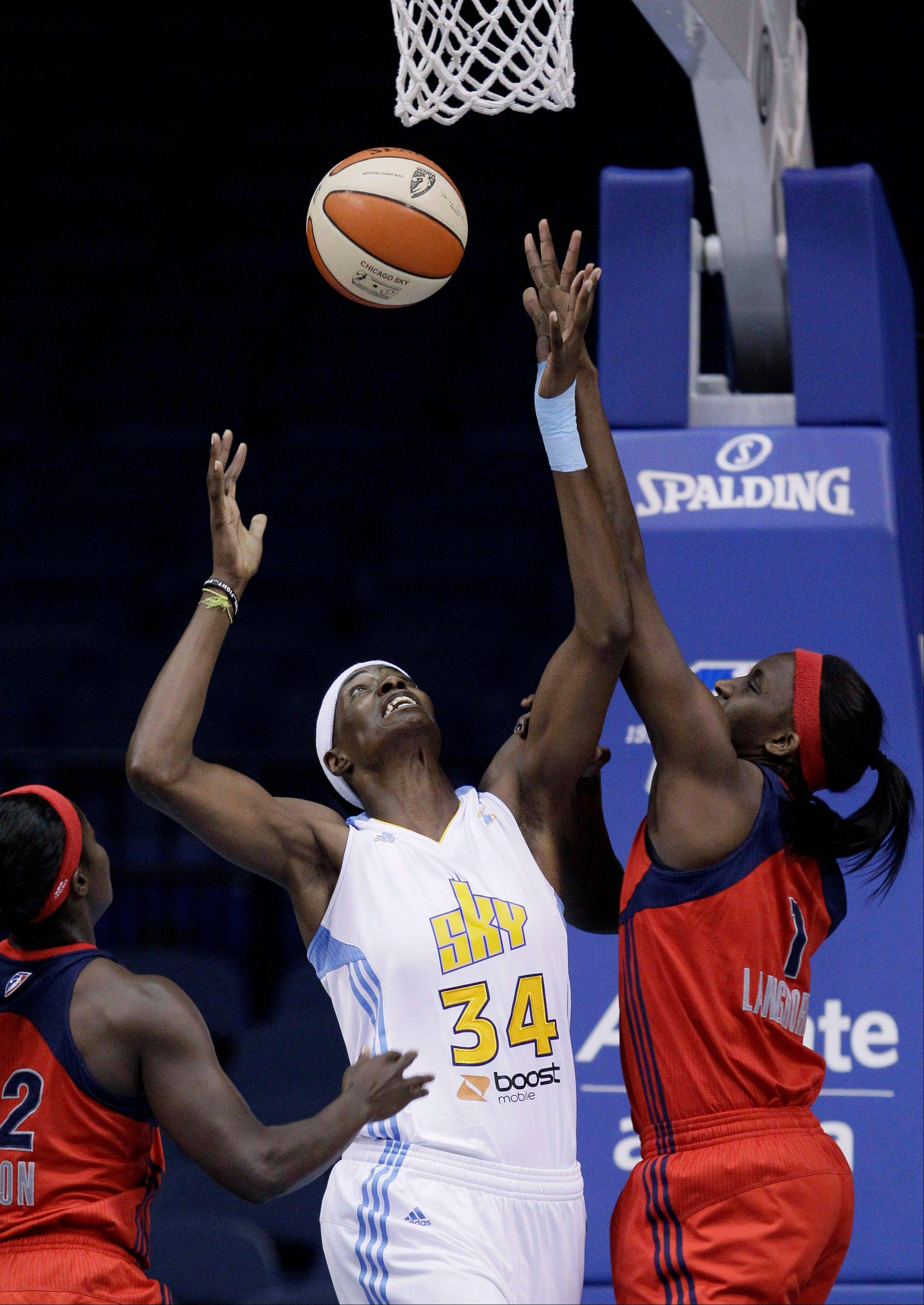 The Sky's Sylvia Fowles battles for a rebound with Matee Ajavon, left, and Crystal Langhorne of the Mystics on Friday.