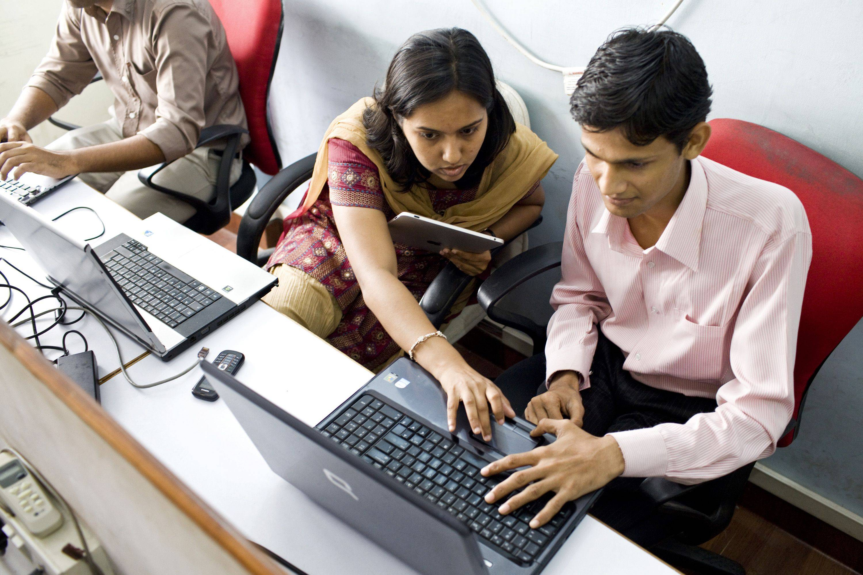 Quality assurance team leader Harshada Baviskar, center, works with a software programmer as they develop applications at the MoFirst Solutions Pvt. office in Mumbai, India.